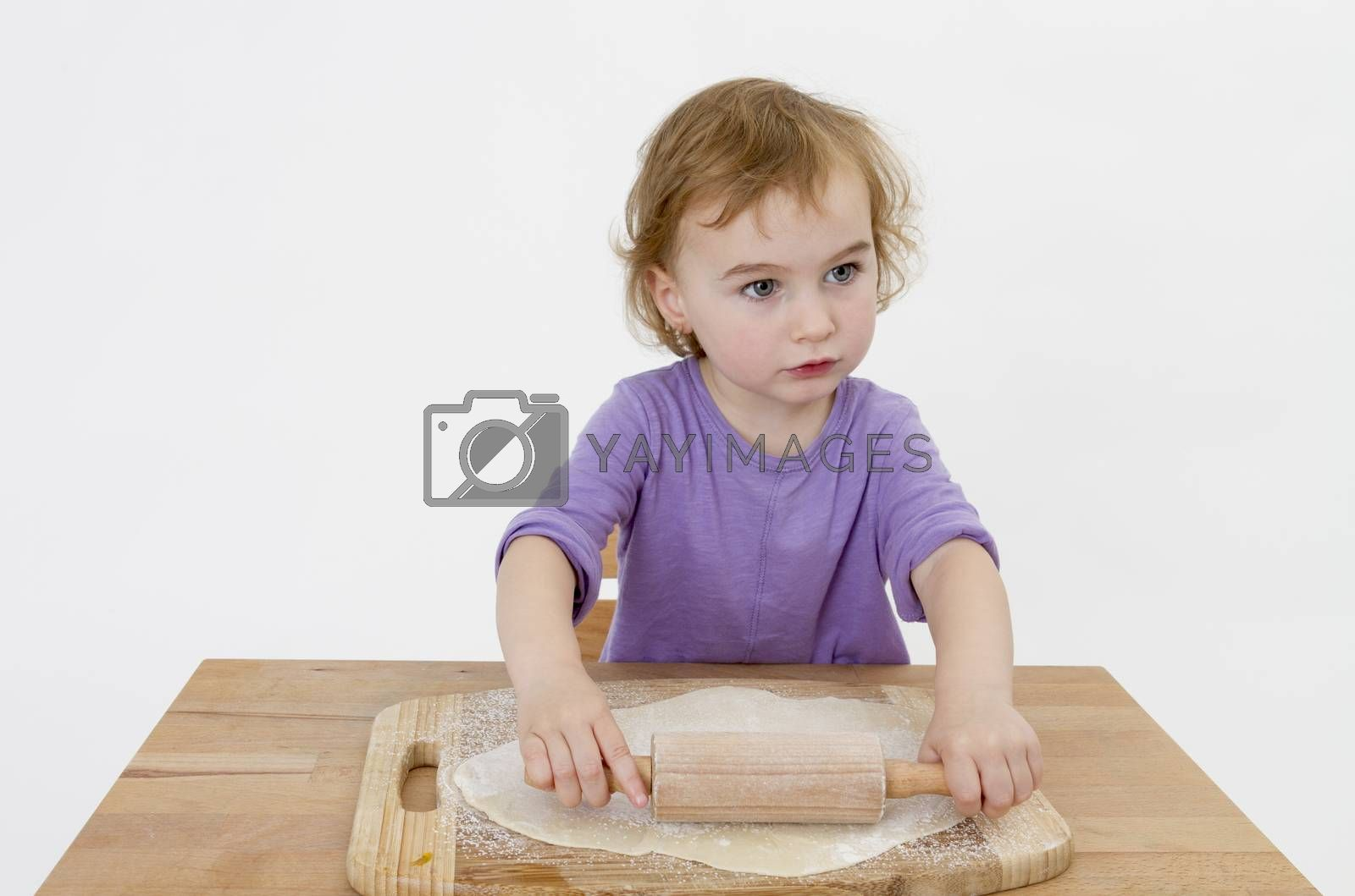 Royalty free image of child rolling out dough by gewoldi
