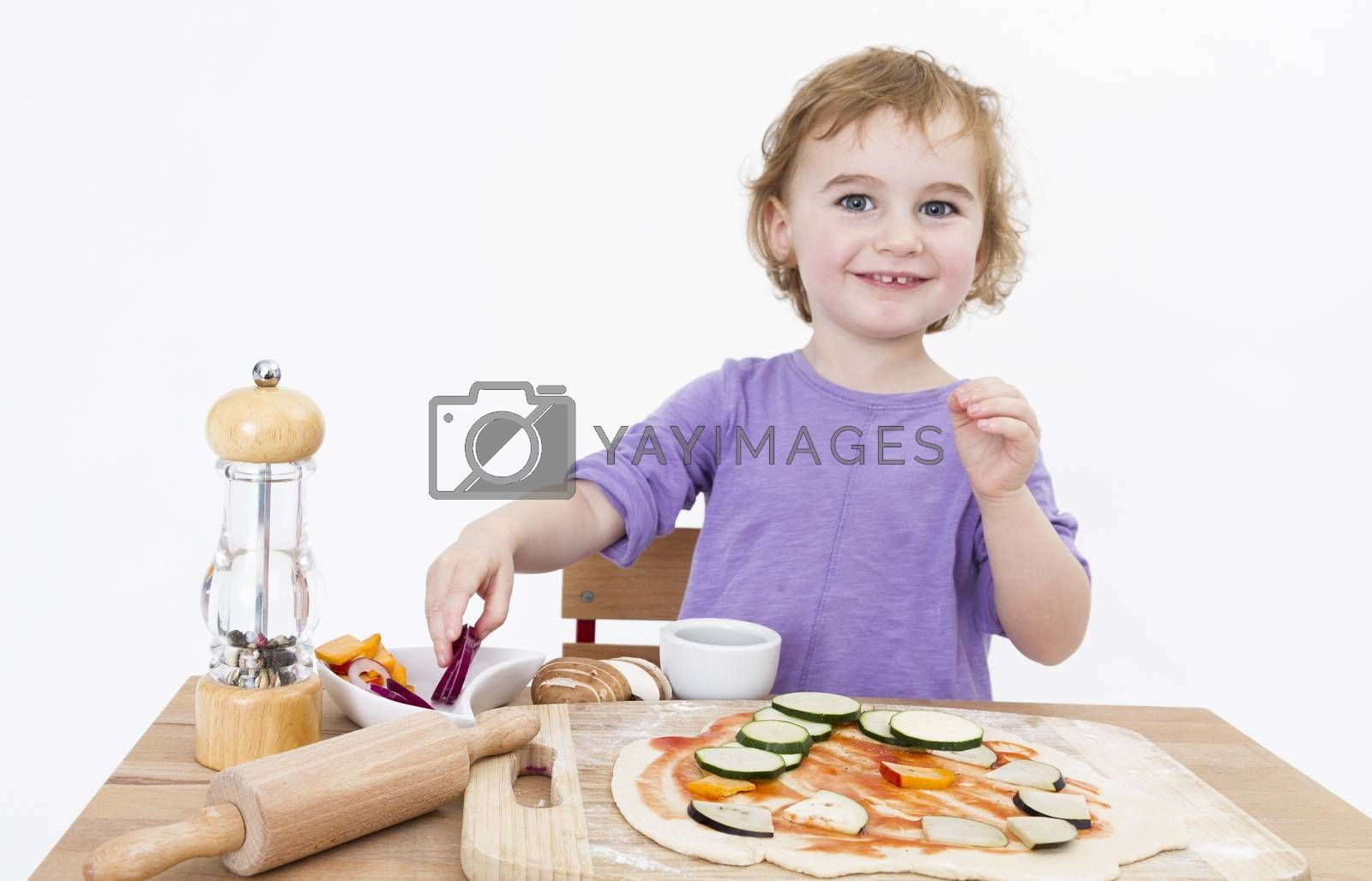 Royalty free image of smiling young girl preparing fresh pizza by gewoldi