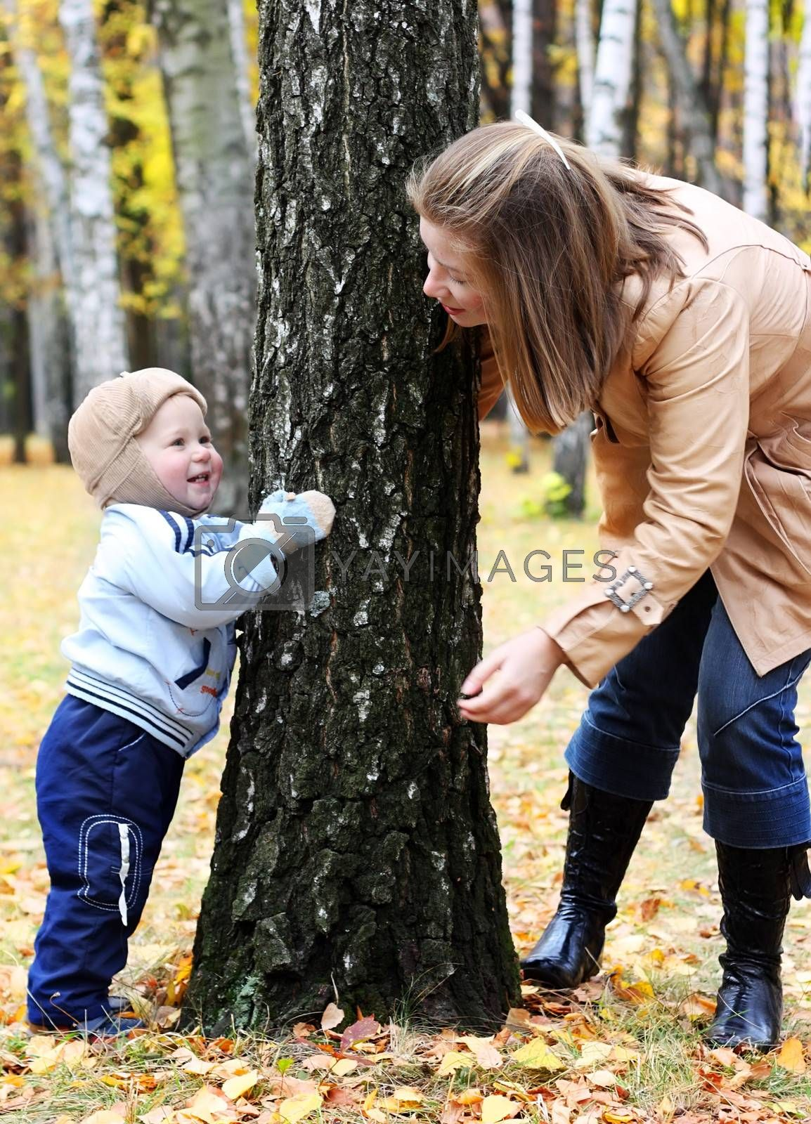 Mother and son play hide-and-seek in a park