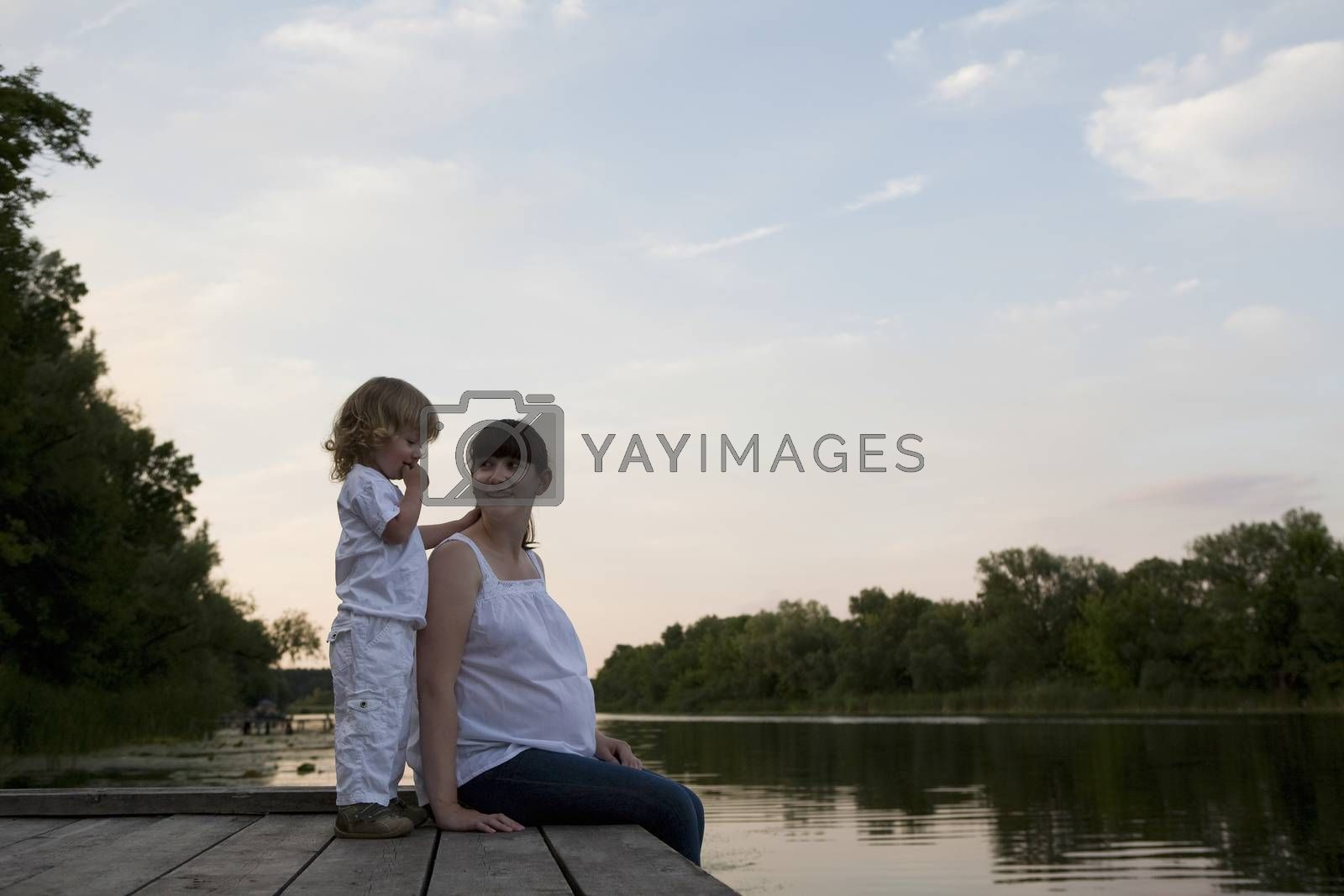 Pregnant Mother And Daughter Sitting On Jetty In Evening by moodboard
