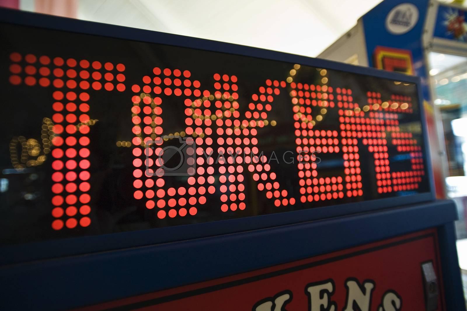 Closeup of token digital game machine at amusement park by moodboard