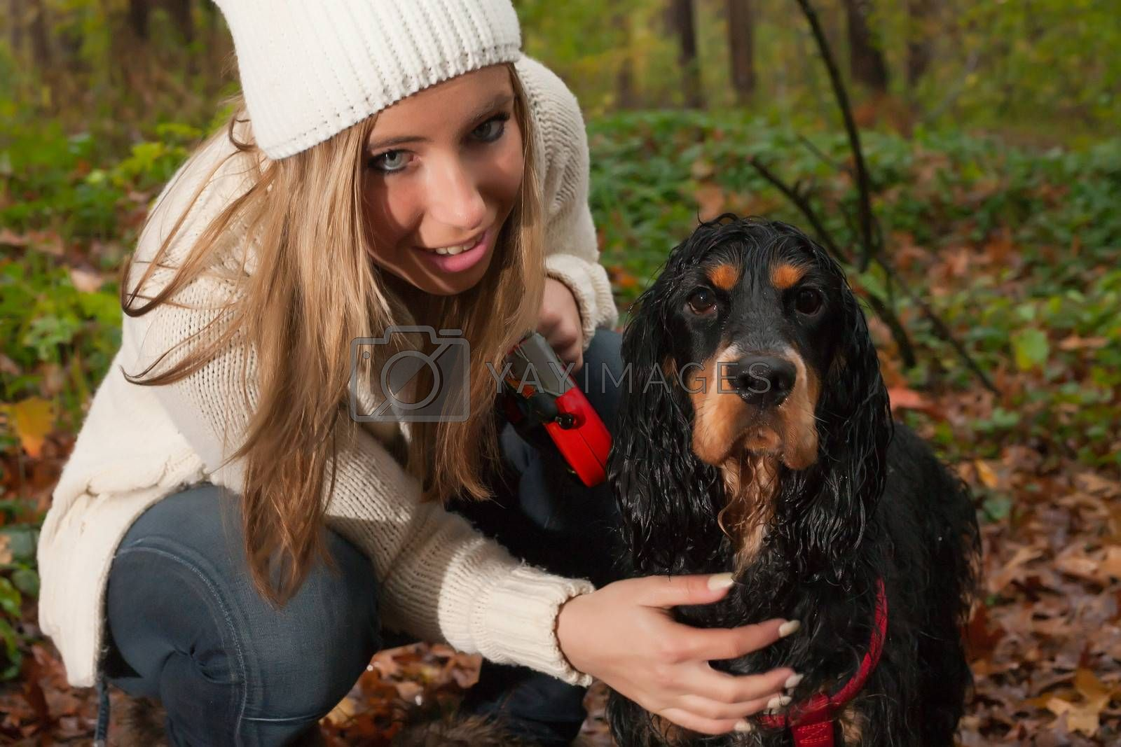 Girl and her dog are having a wet time in the rain