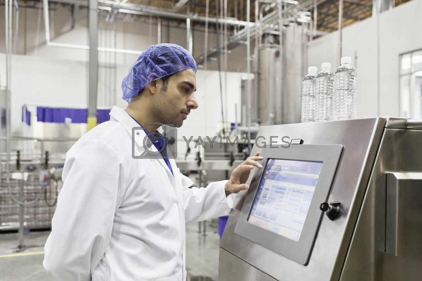 Industrial worker at bottling machine