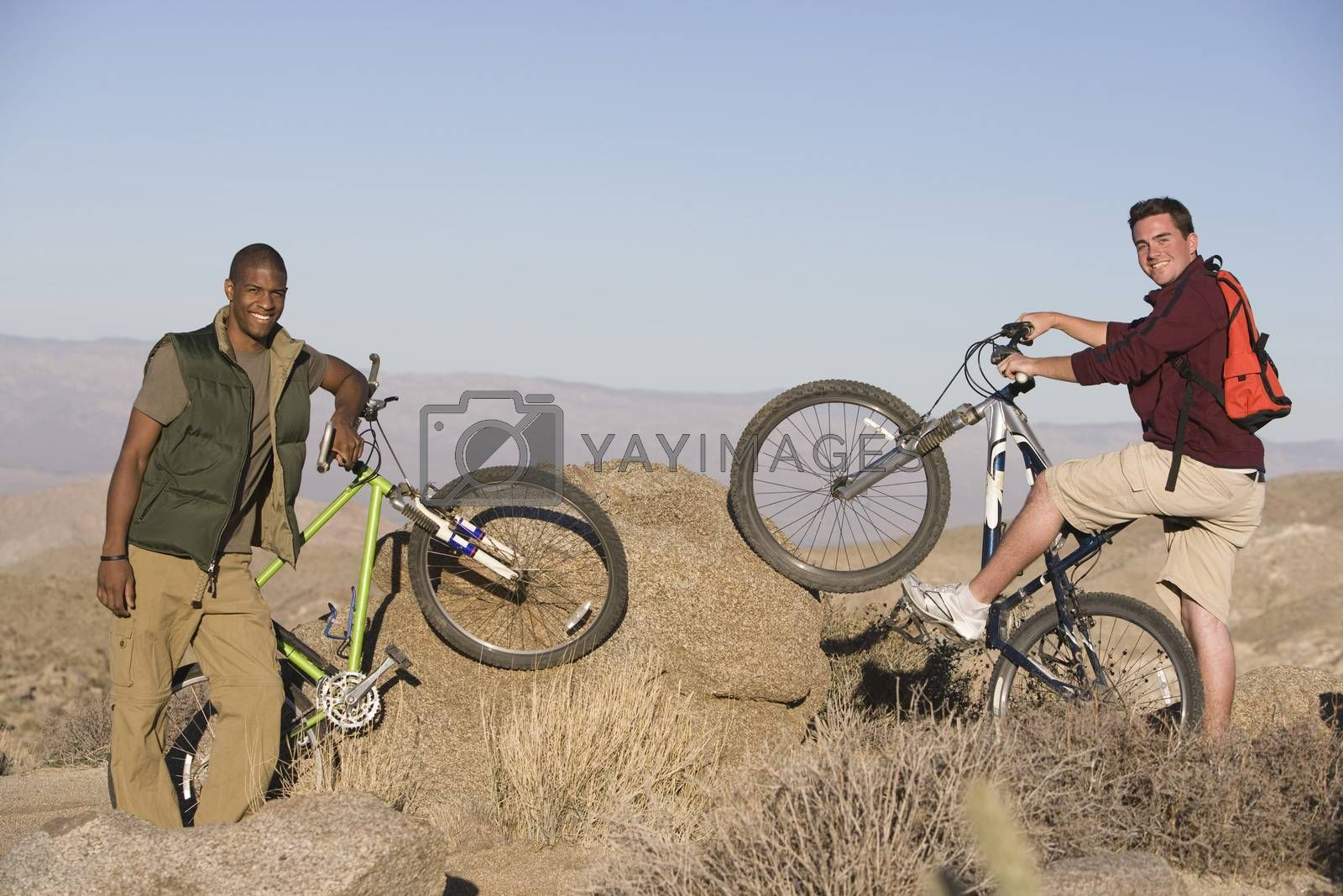 Male Friends With Mountain Bikes On Rocks