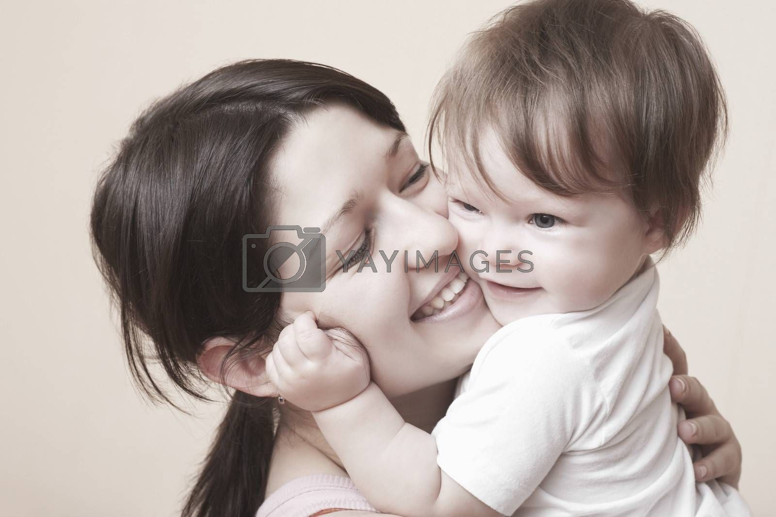 Mother laughs and squeezes her toddler