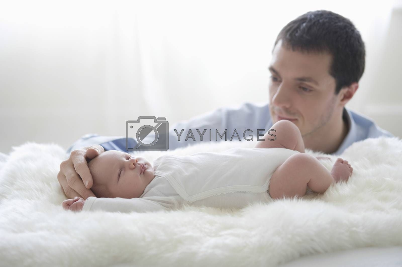 Father holds two week old newborn babies head
