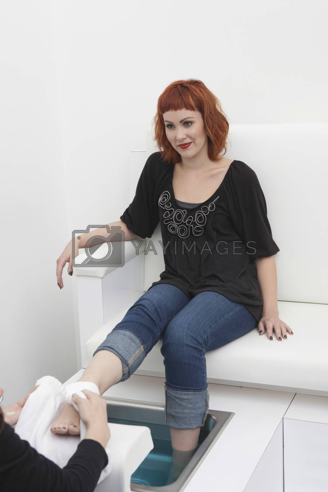 Foot masseuse and client in beauty salon