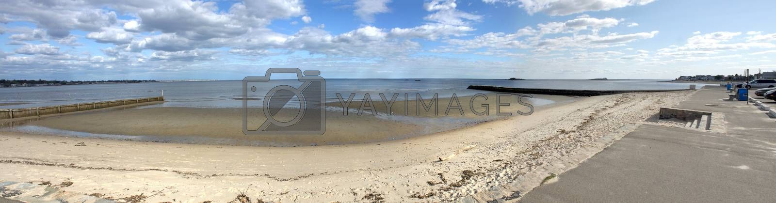 Wide angle panoramic view of a public Connecticut beach during low tide.
