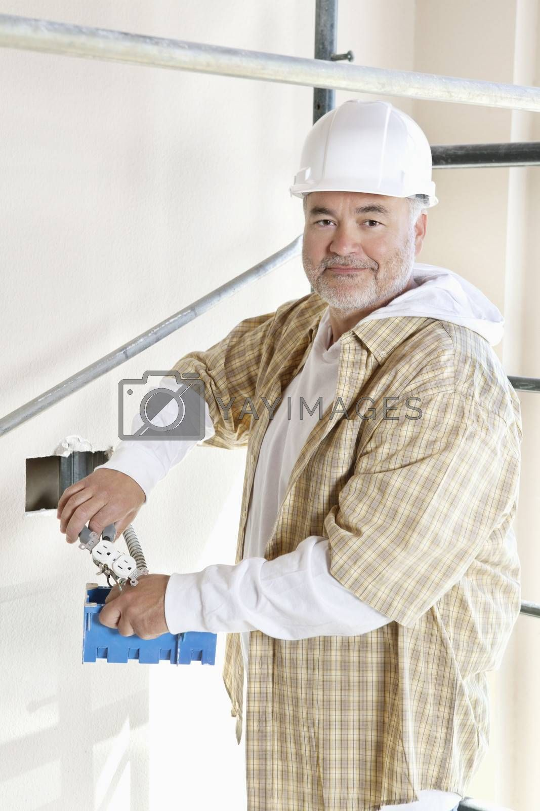 Portrait of a mature man holding construction equipment