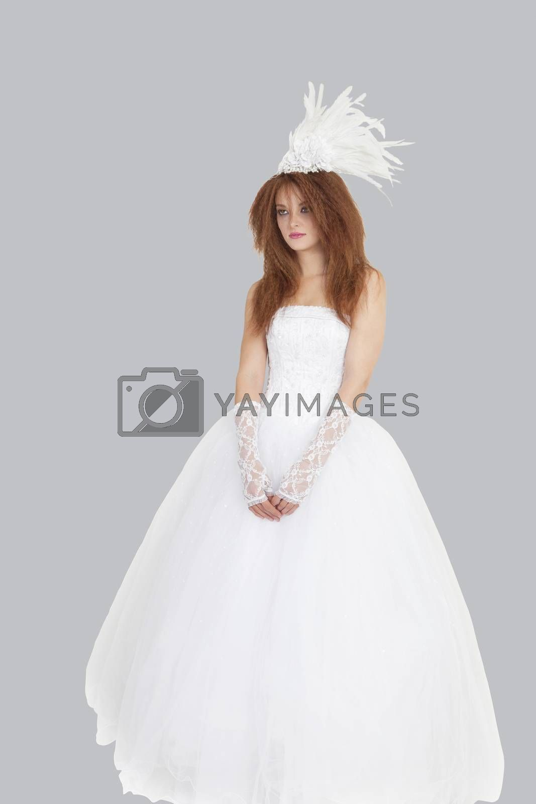 Young brunette bride standing in wedding gown over light gray background