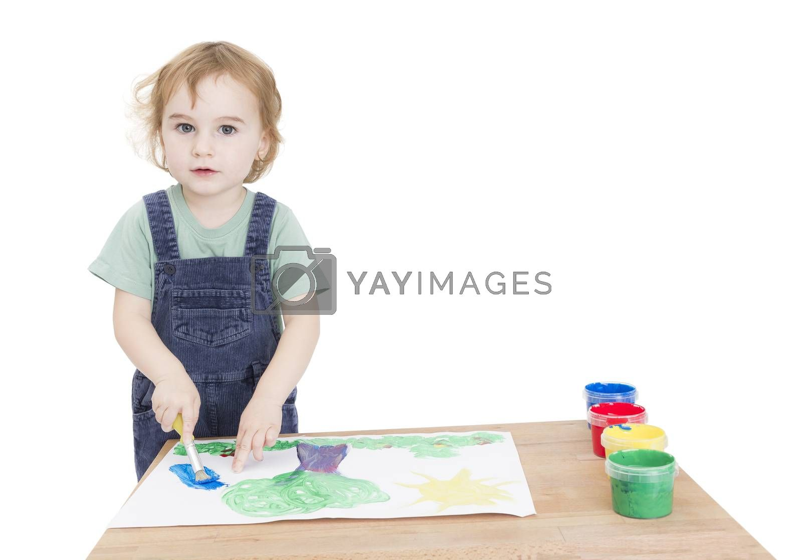 cute girl painting on small desk in grey background. studio shot