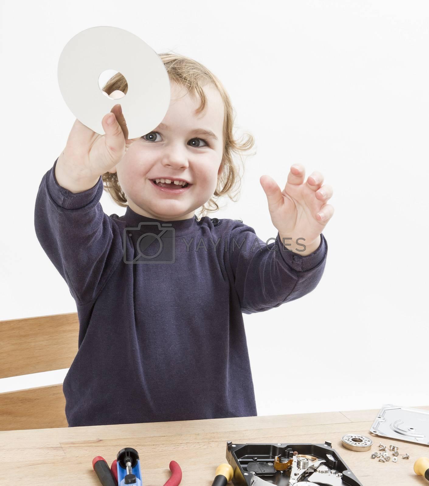 child repairing computer part. studio shot in light grey background