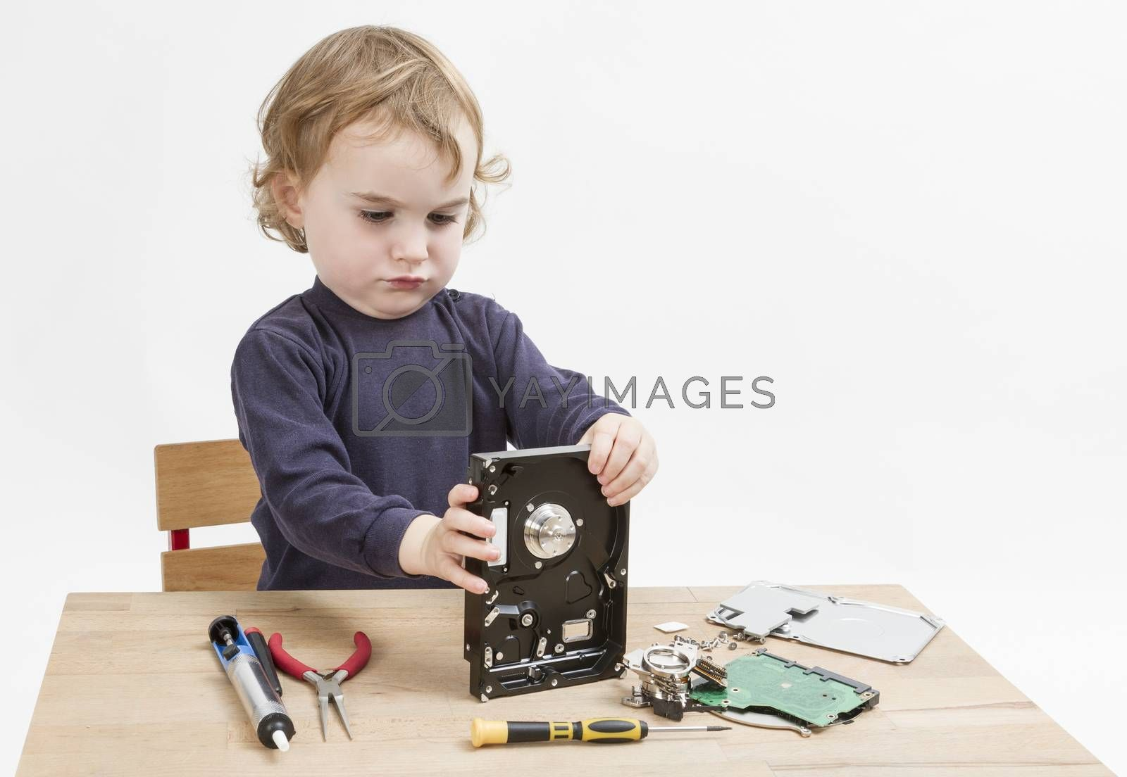 young child repairing open hard disk drive with different tools