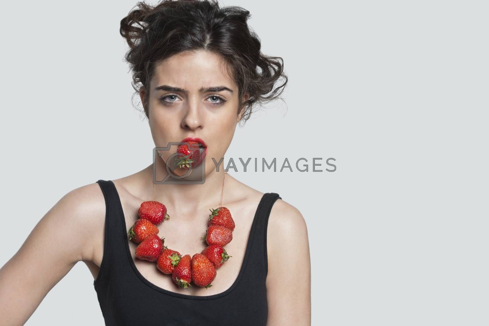 Portrait of a young woman wearing strawberry necklace while biting one piece over gray background