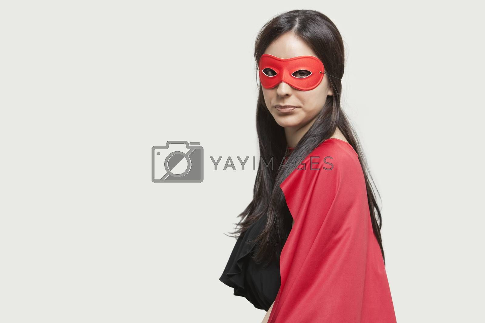 Portrait of young woman in superhero costume against gray background
