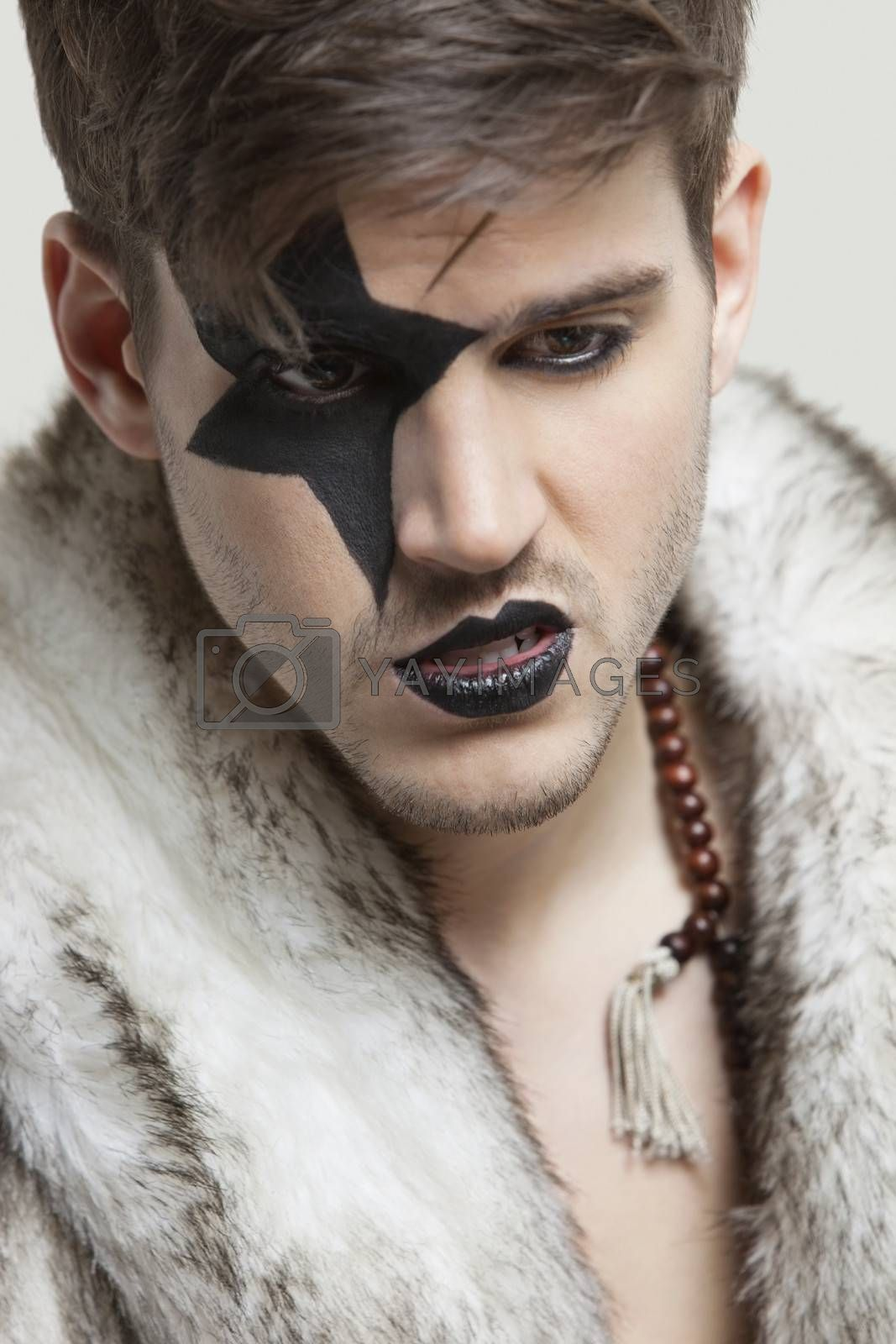 Angry young man with painted face wearing fur coat against gray background