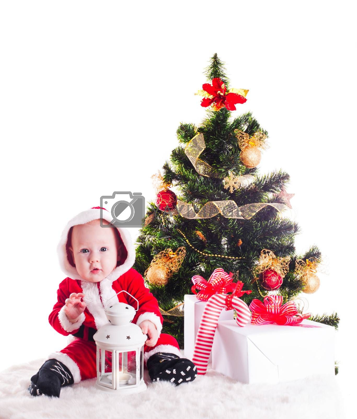 Christmas baby under the New Years tree with gifts