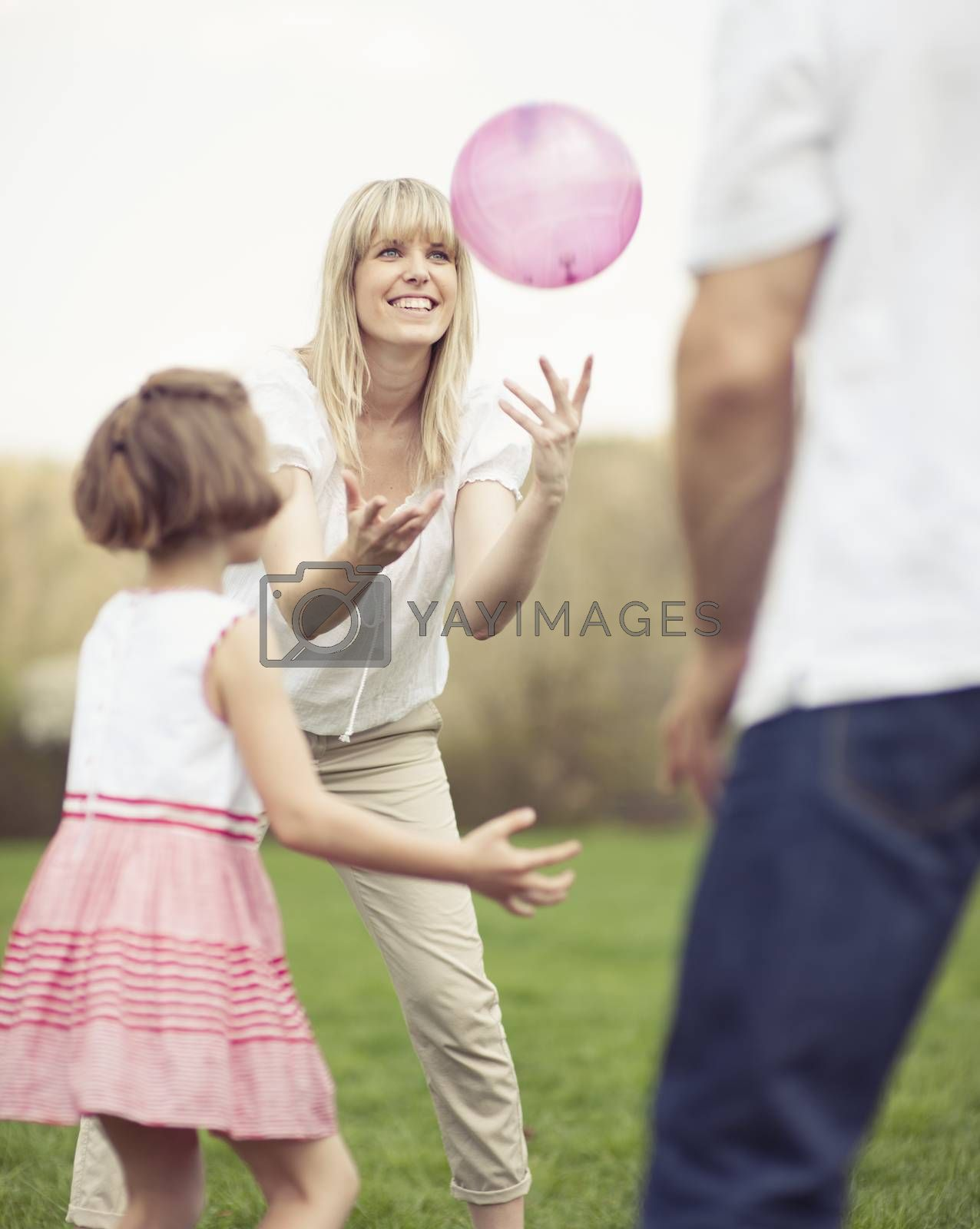 Father mother and daughter throwing ball to each other in the park