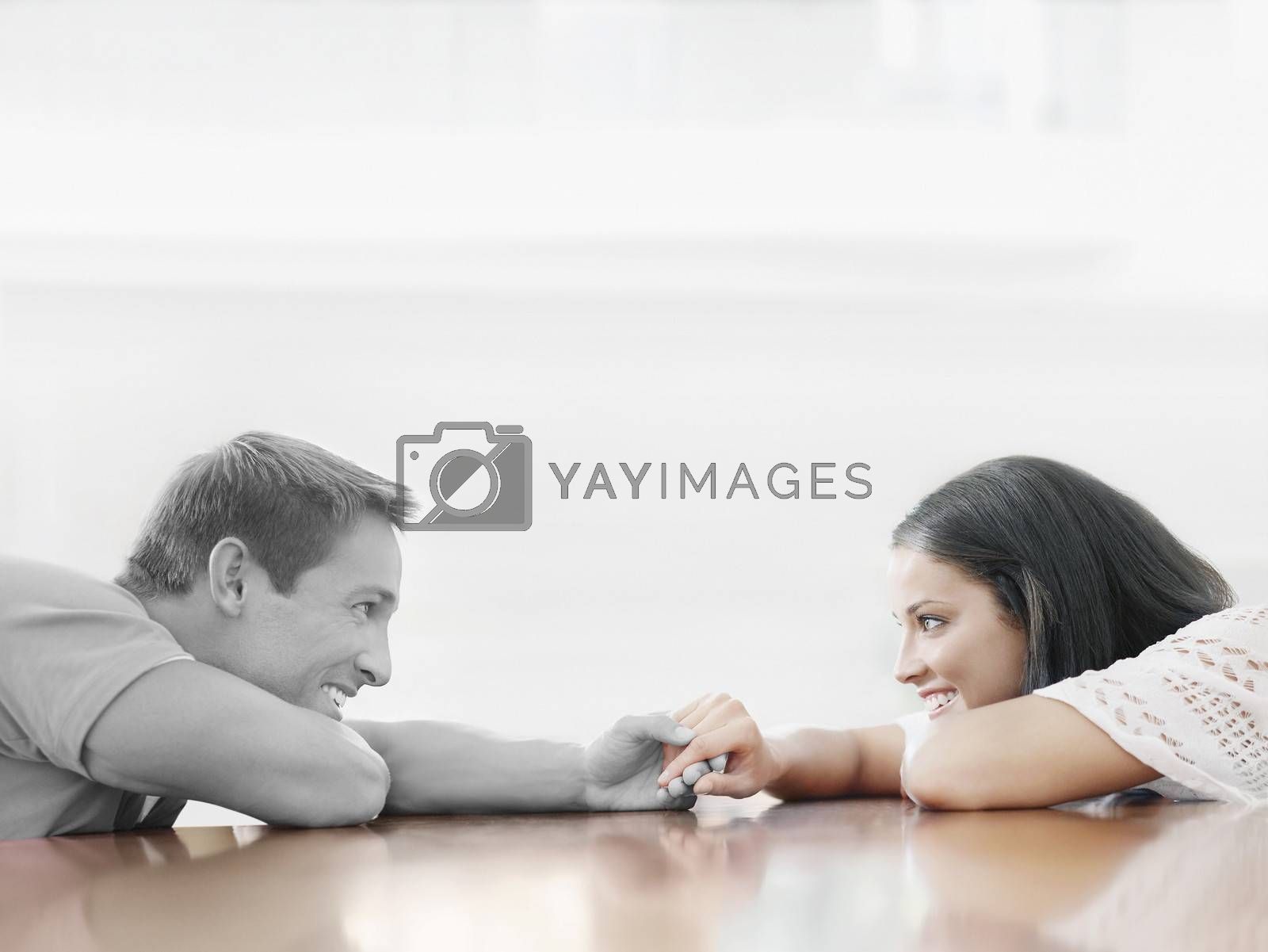 Affectionate young couple holding hands across table