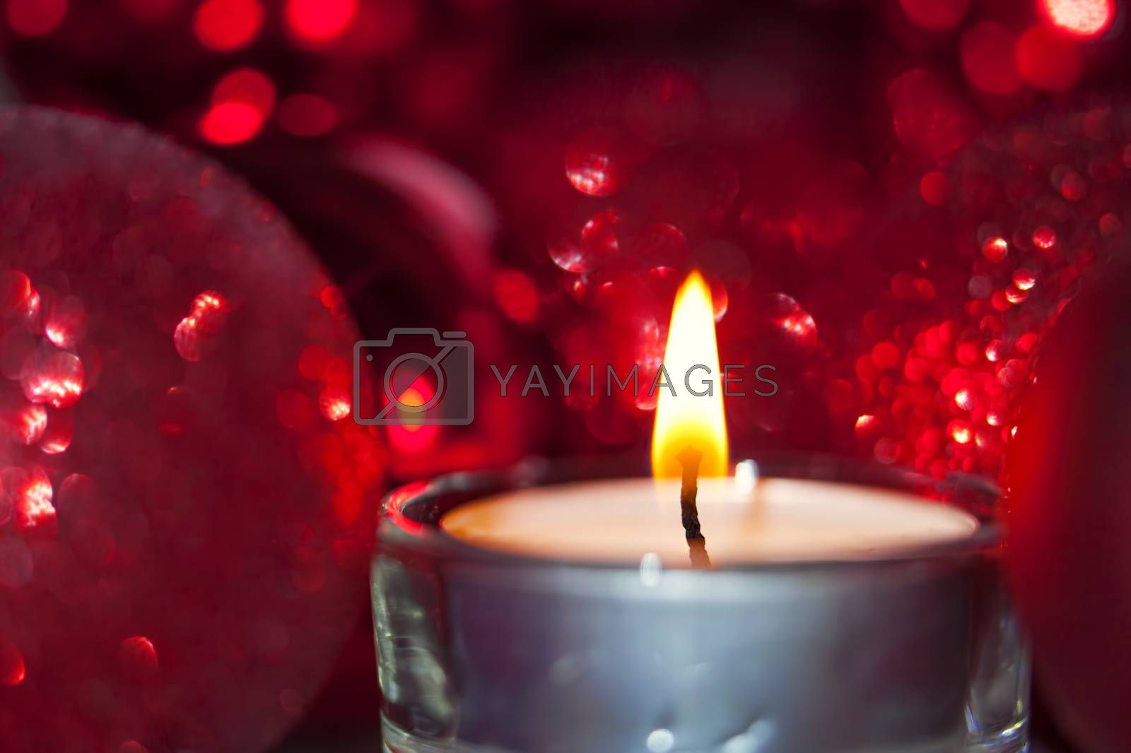 Close-up of christmas baubles and candle light