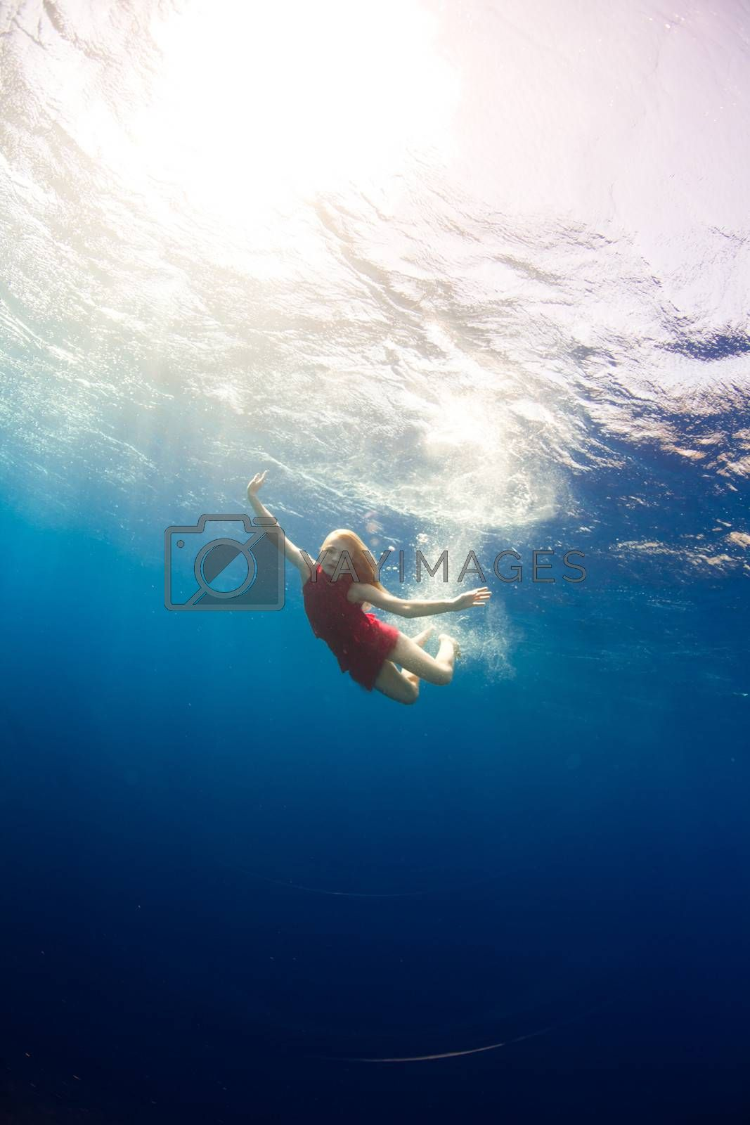 beautiful girl diving under the sea