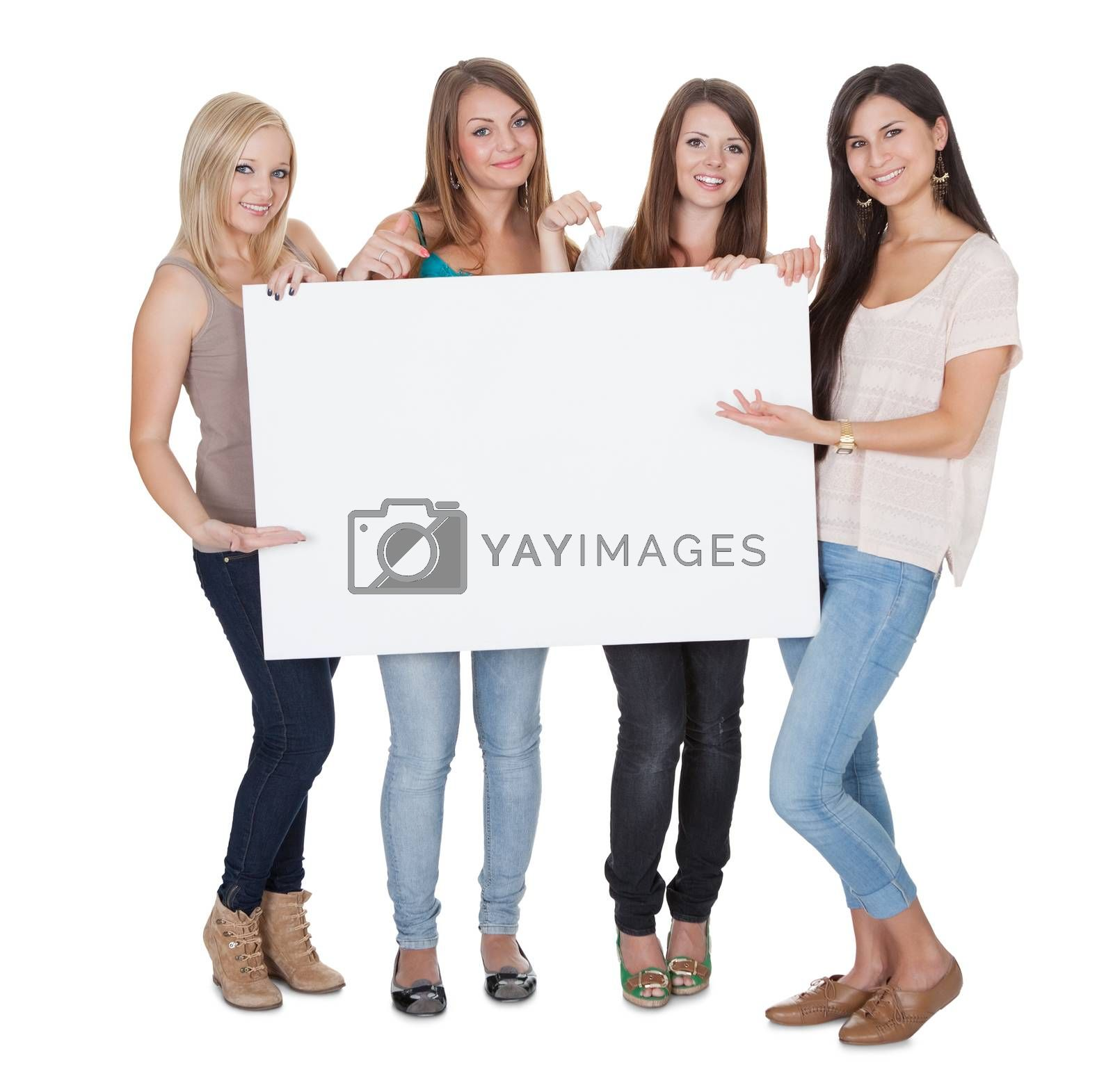 Studio shot of four attractive girls with a blank white board isolated on white