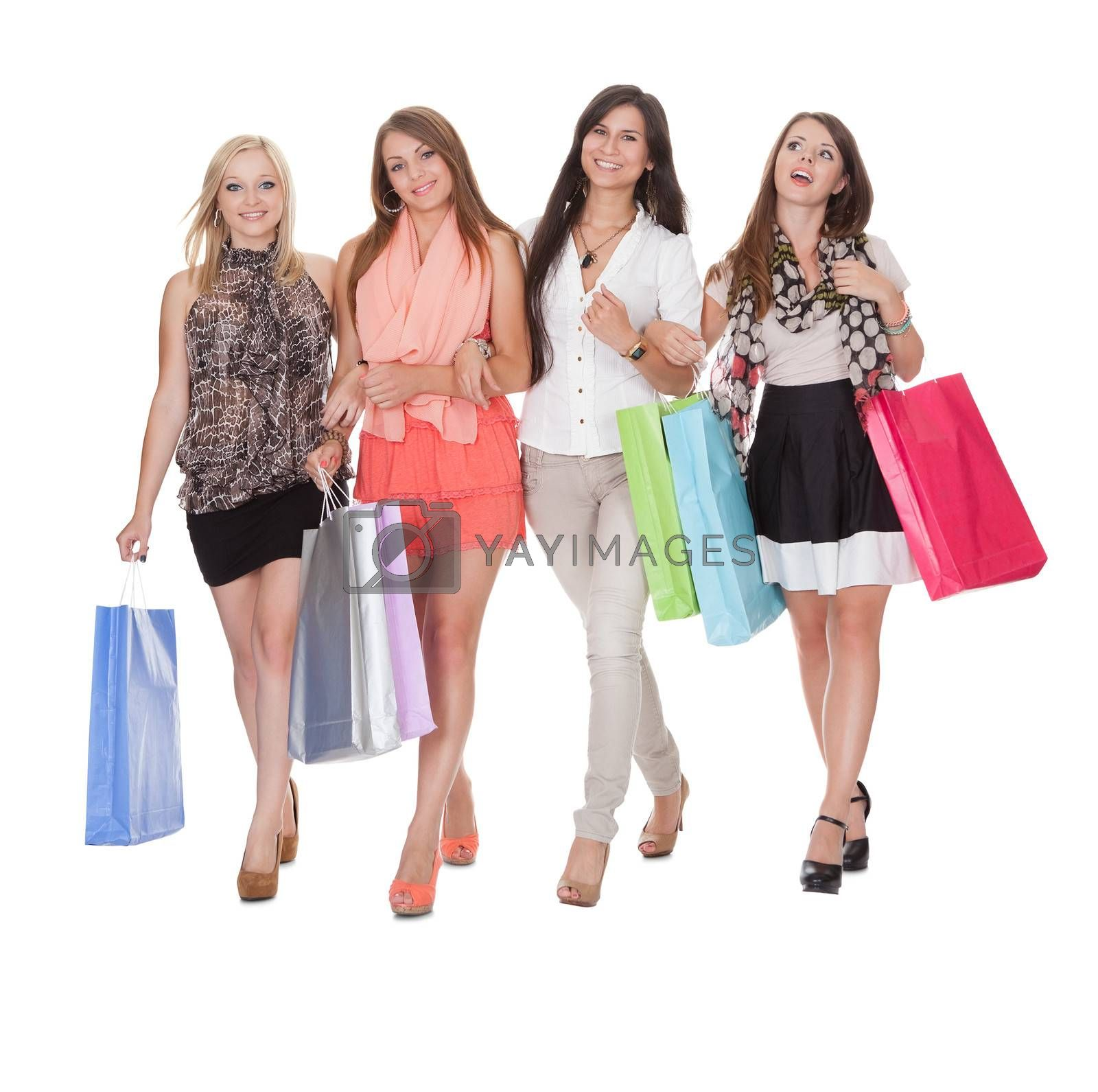 Four happy women returning from shopping by AndreyPopov