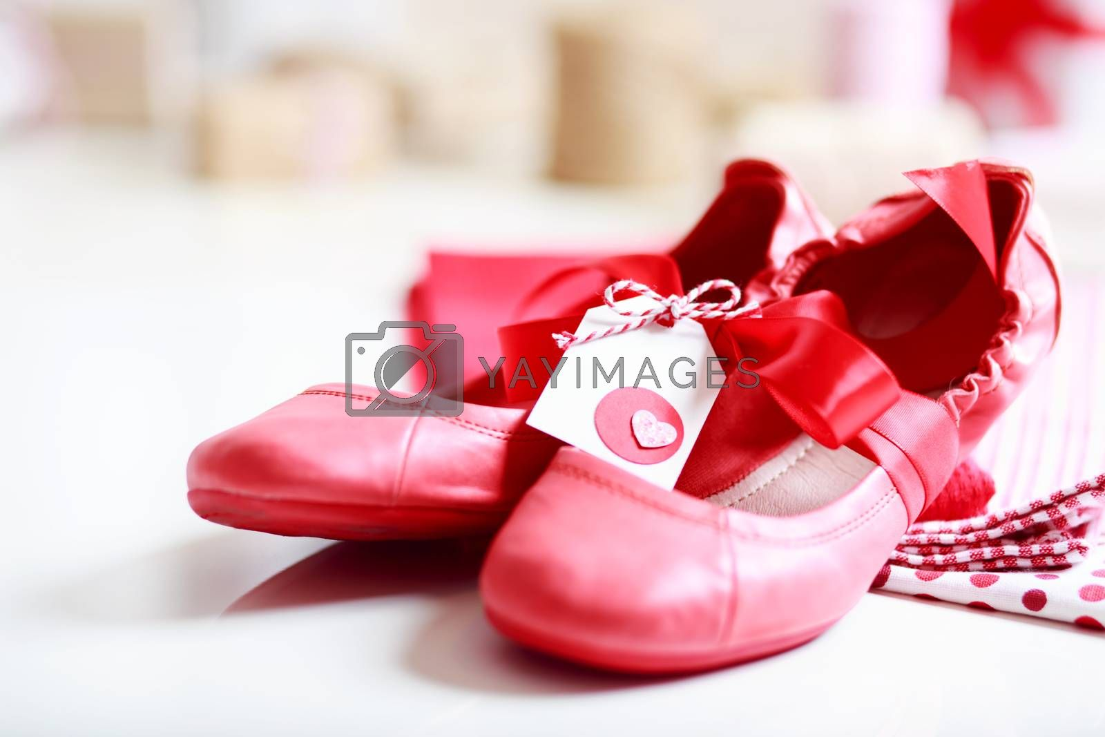 Royalty free image of Red shoes with ribbon and heart tag by melpomene