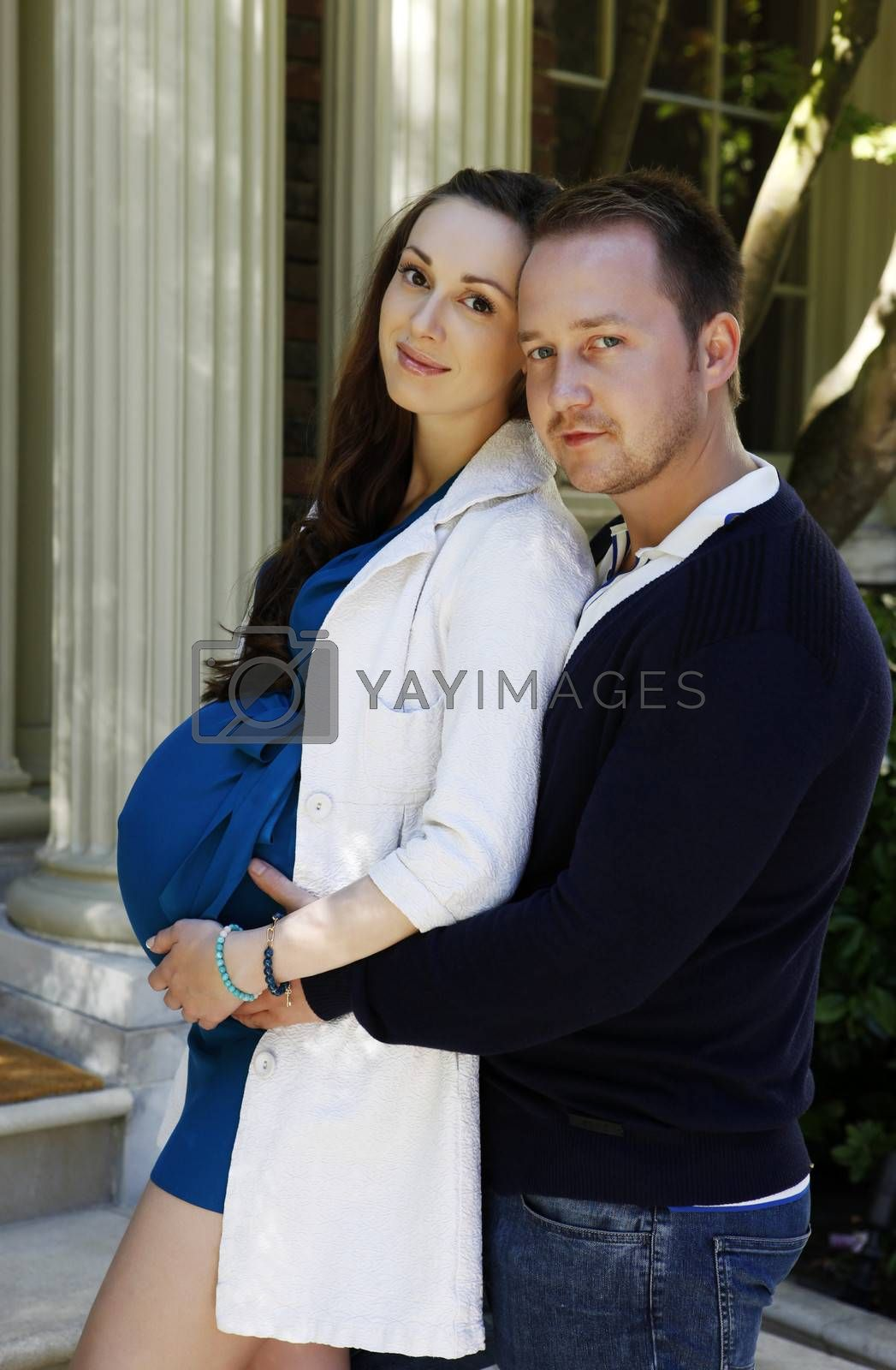 Happy beautiful pregnant woman with his husband on the outside