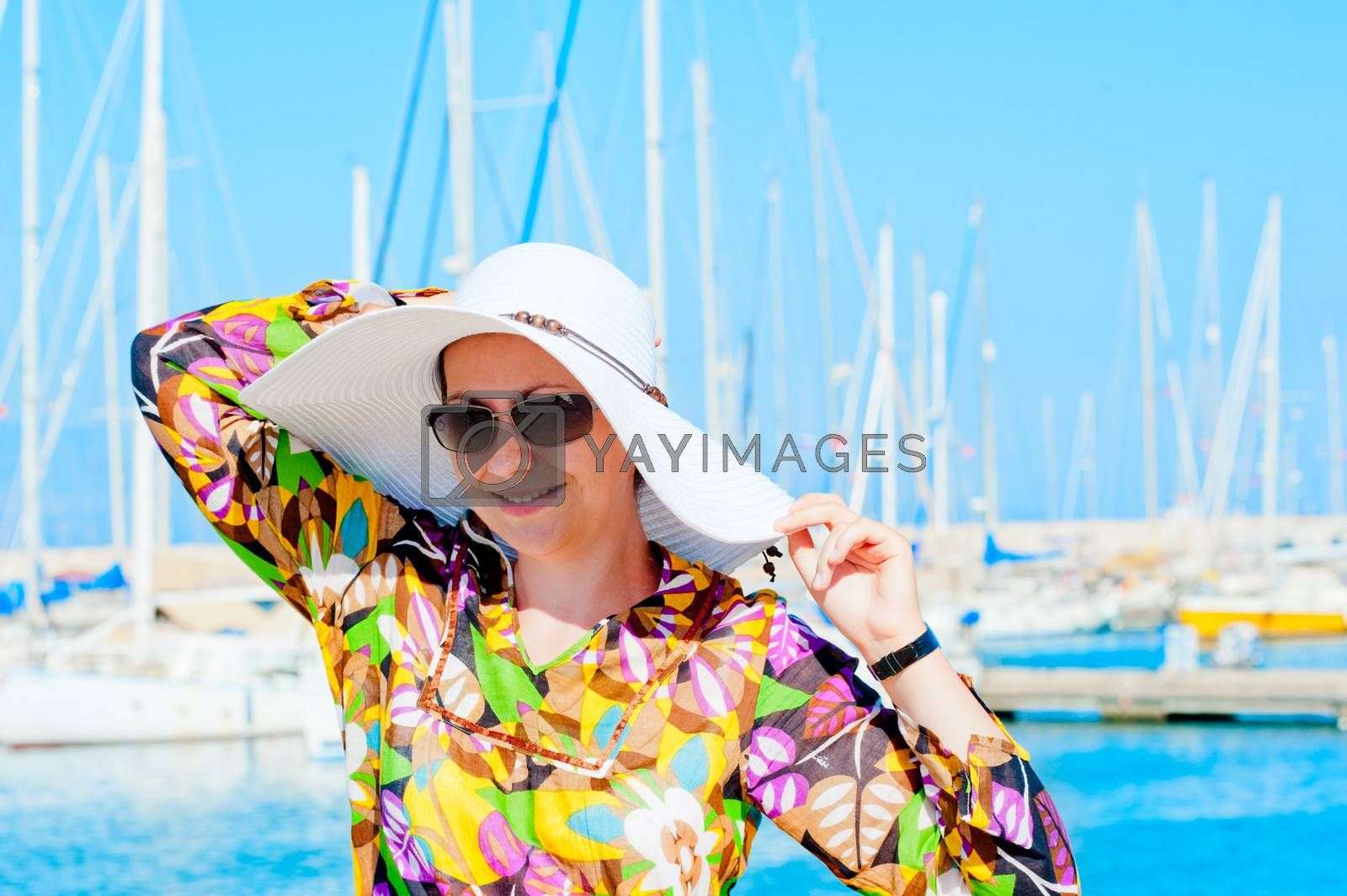Portrait of a woman in white panama hat on a background of yachts