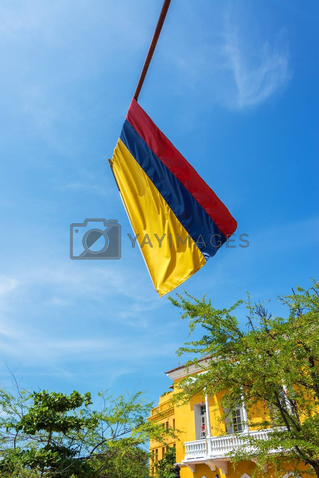 Colombian flag in the old town of Cartagena, Colombia with blue sky and colonial architecture