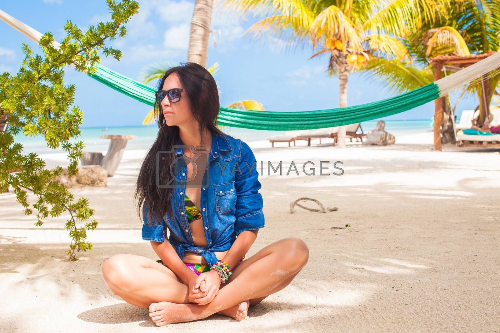 Young woman in lotus position on white sand beach