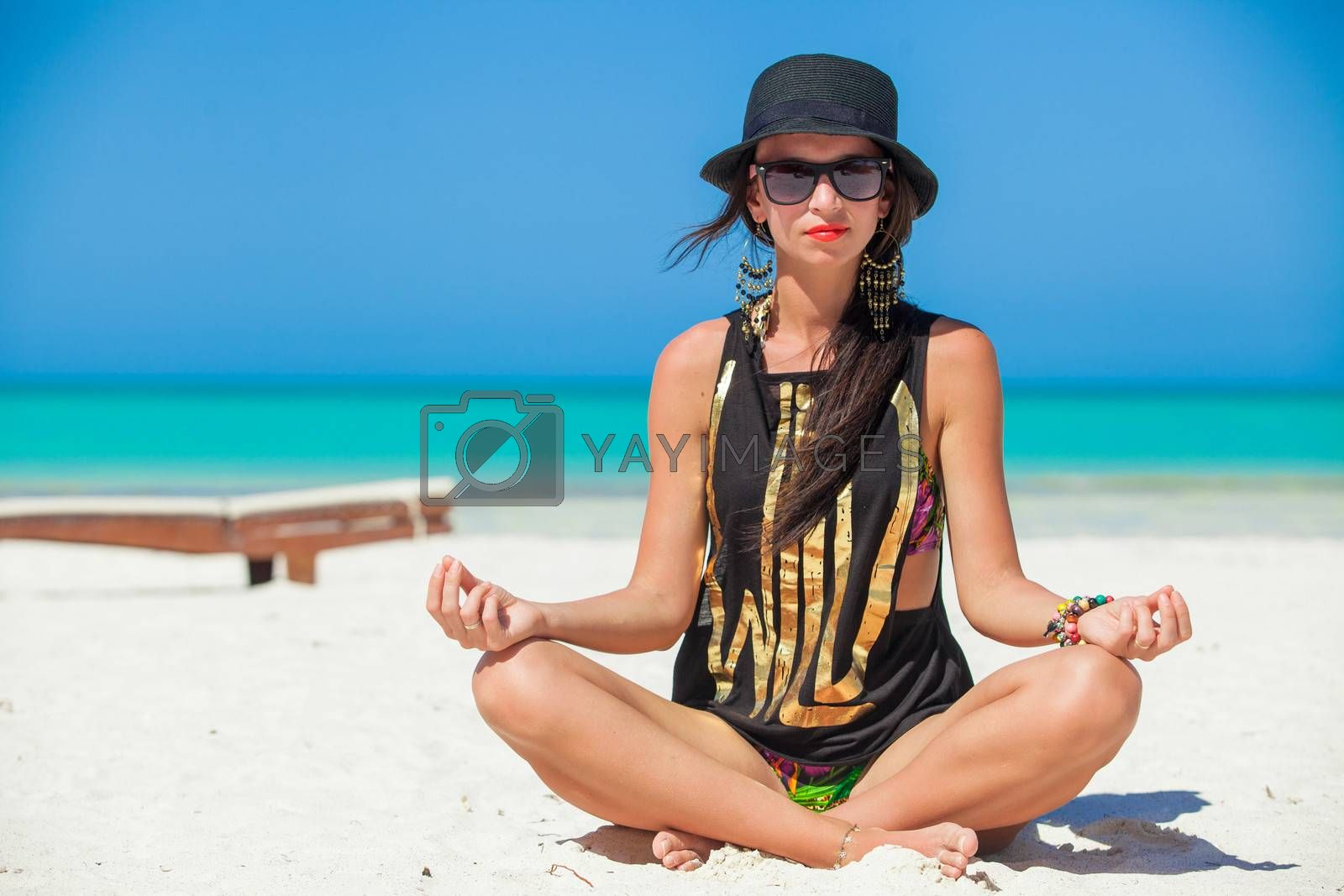 Young sexy woman sitting in the lotus position on white sand