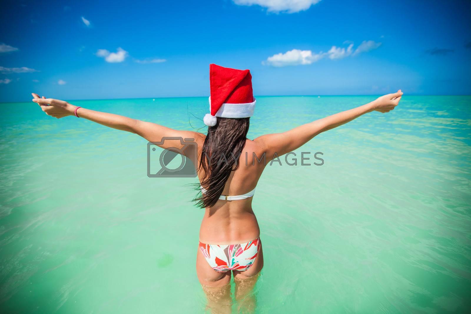Back view of beautiful girl in santa hat walking like a bird