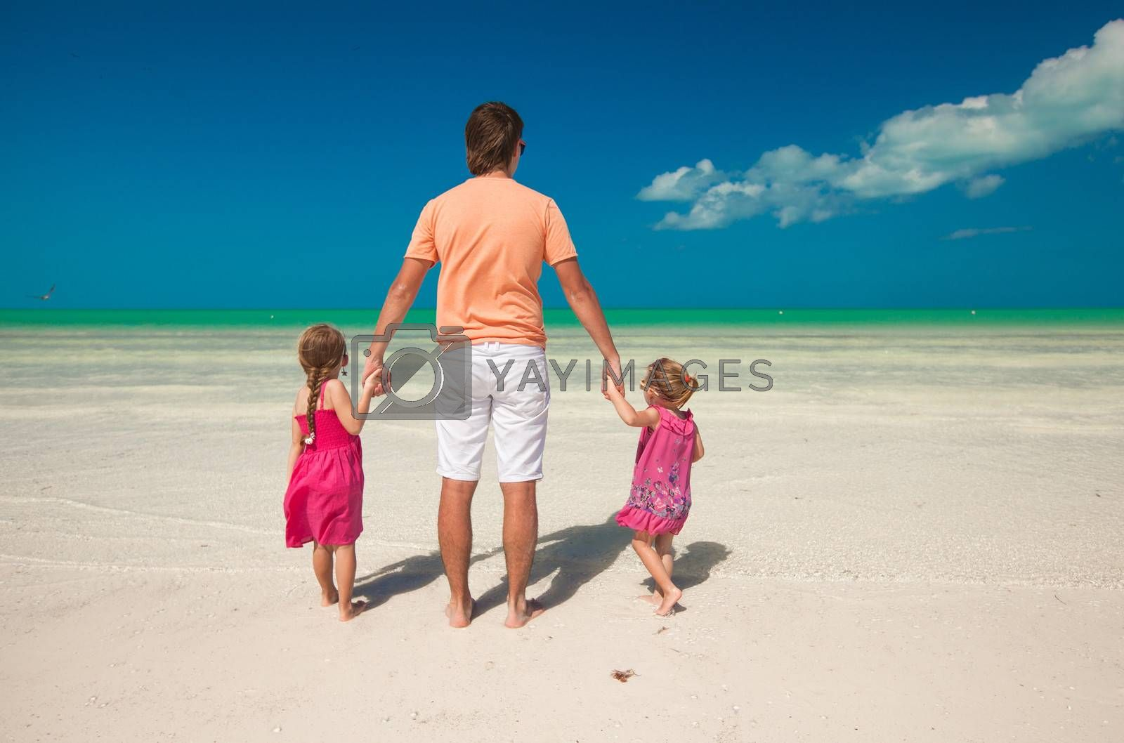 Rear view of young father and Rear view of young father and his two adorable daughters on an exotic vacation