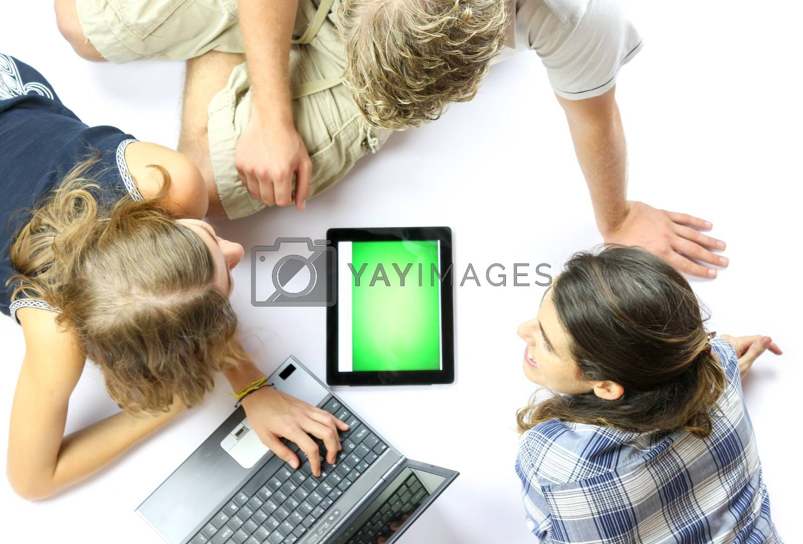 A group of young students using a laptop and an electronic tablet