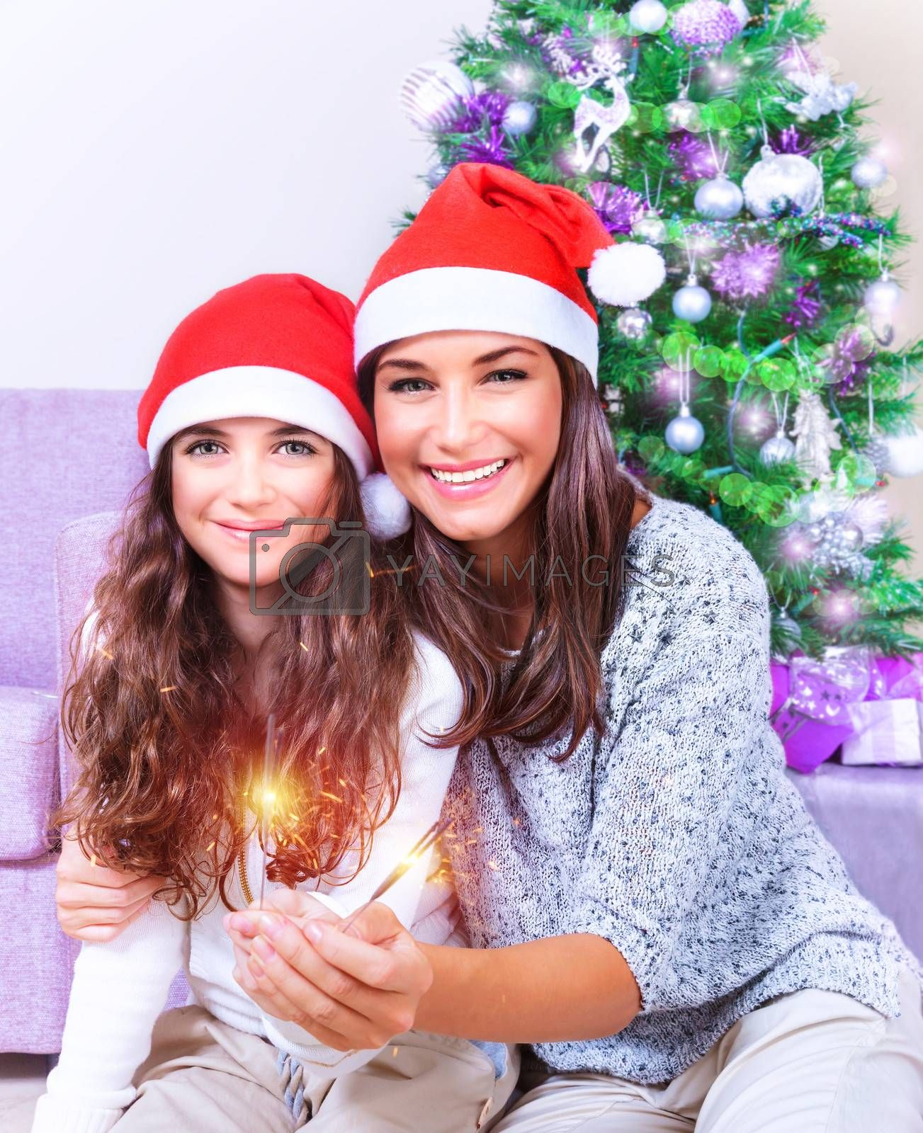 Portrait of young mother with teenage daughter burning bengal fire at home, having fun on Christmas eve, New Year celebration concept