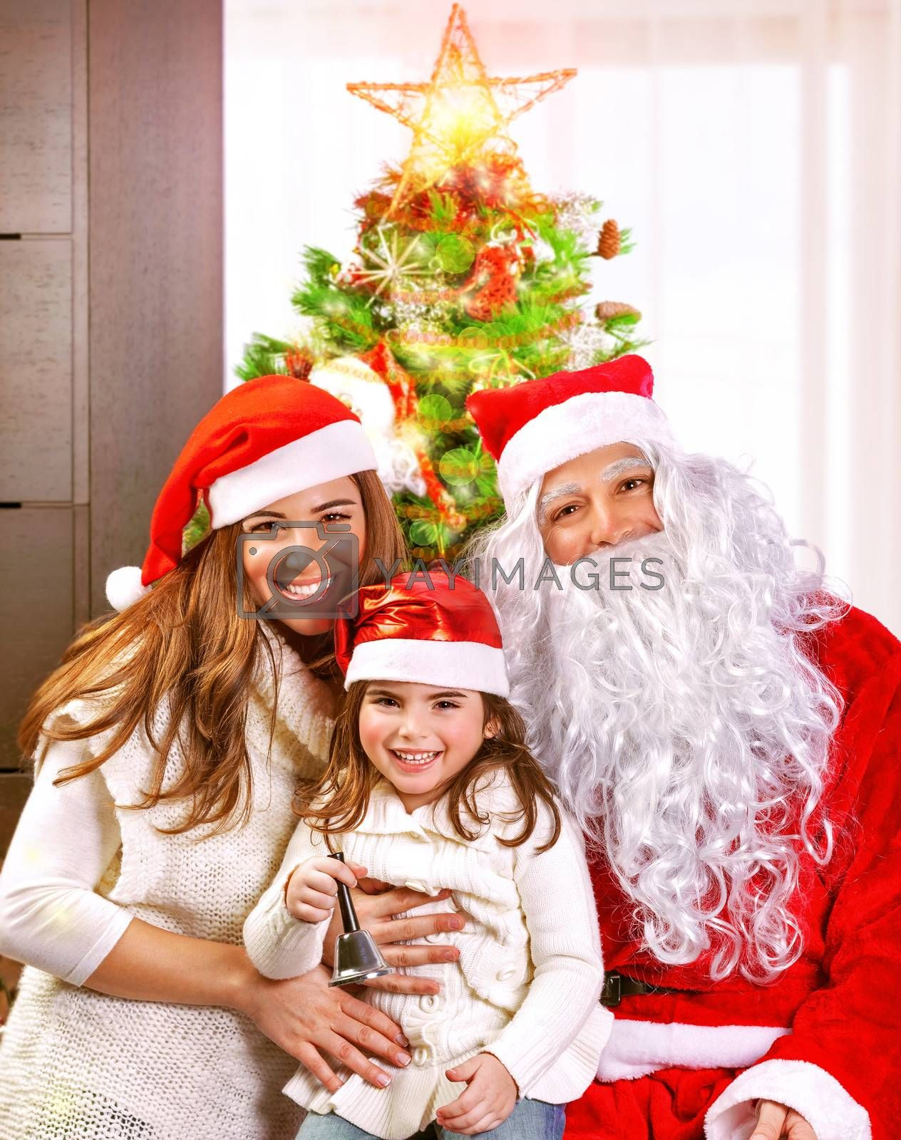 Happy cheerful young family celebrate Christmas holiday at home, little girl with mother and father wearing Santa Claus costume