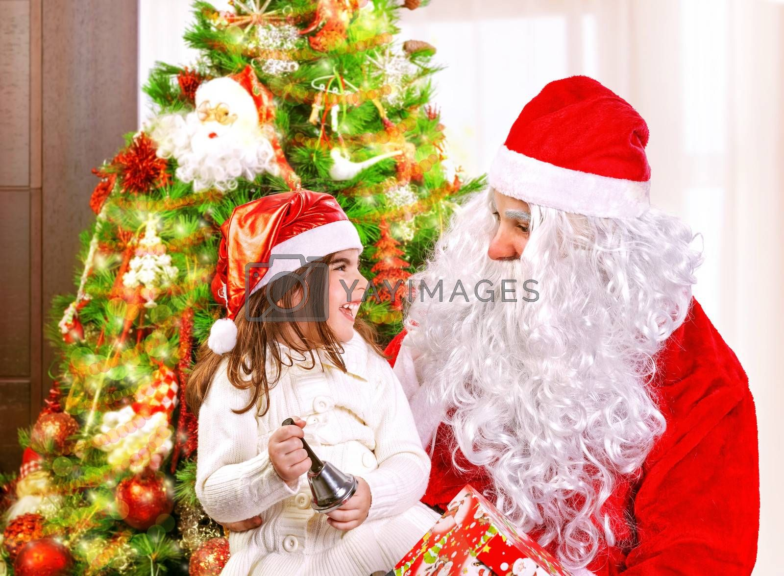Cute little girl with Santa Claus near Christmas tree at home, having fun, laughing and ringing festive bell, enjoying New Year party