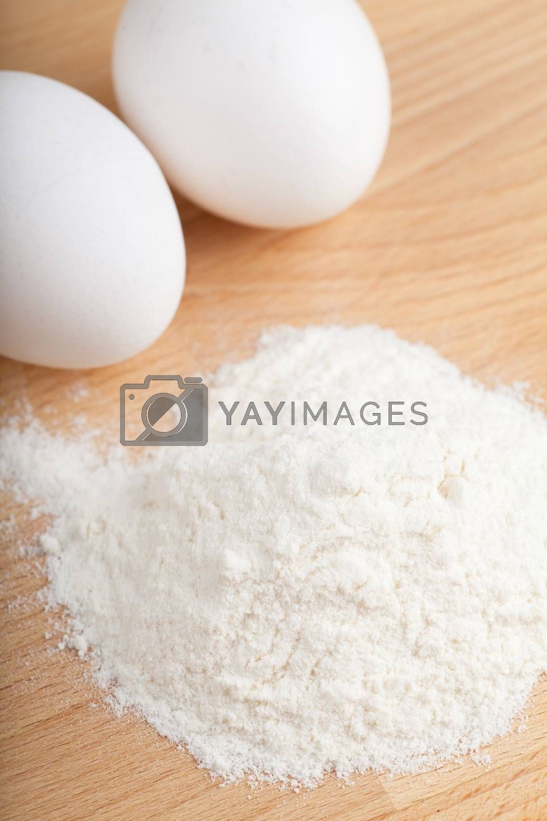 Closeup view of eggs and flour on a wooden table