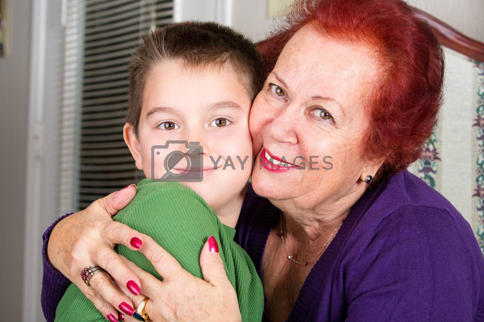 Grandmother's Love to her eight years old grandson, she hugs him tighly with a cheek to cheek touch while looking at you