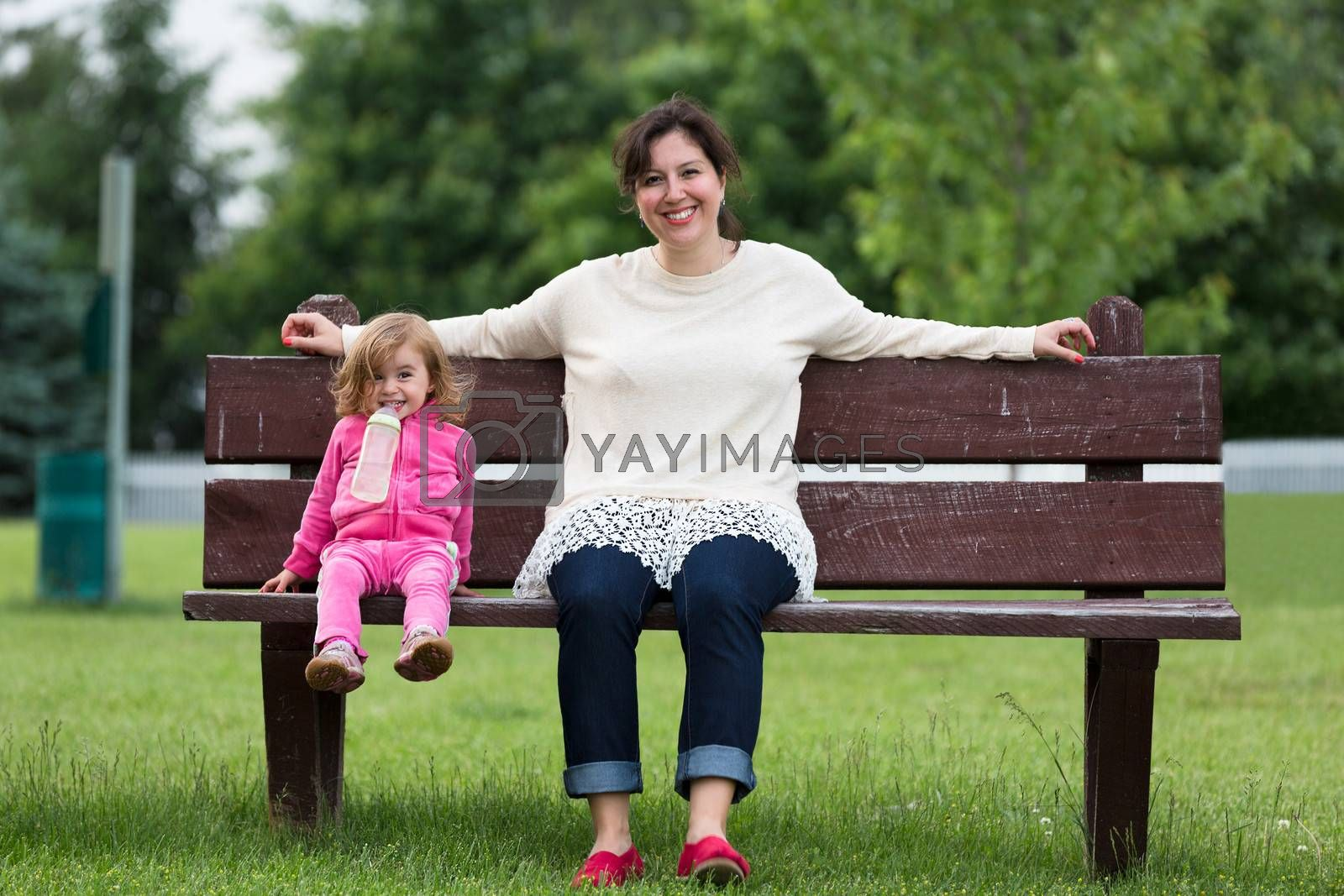 Mother and her toddler daughter having fun trustful moments outside on the bench