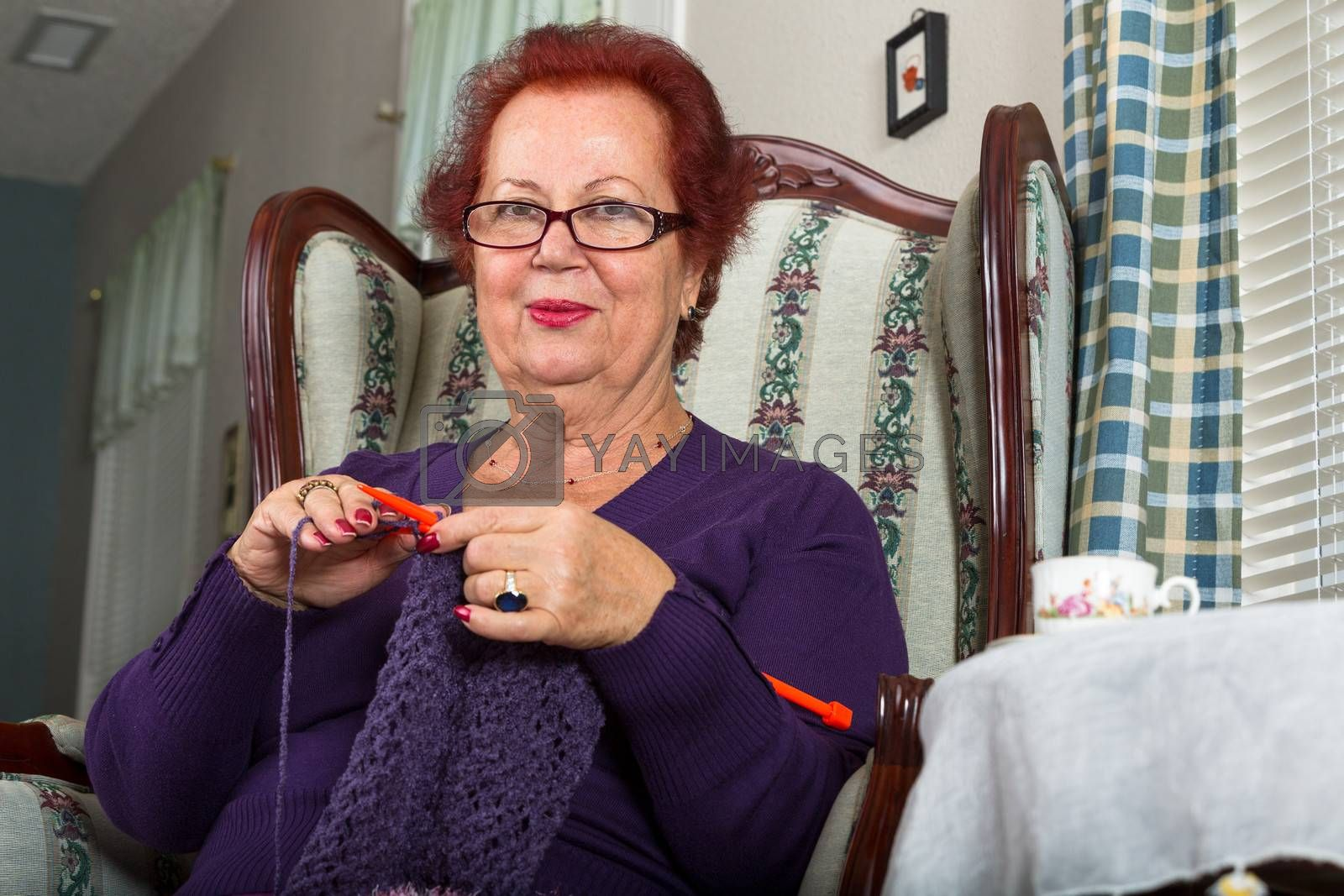 Red haired senior lady looking at you right bewlow her glasses while crocheting her purple scarf
