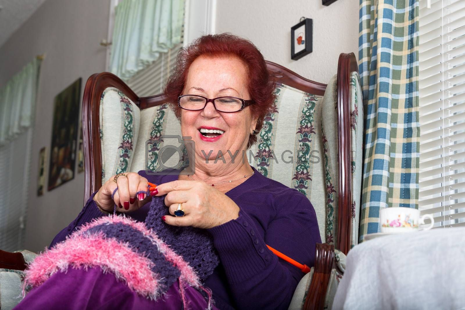 Senior happy woman laughing while knitting, she sits on a fancy old classic style chair