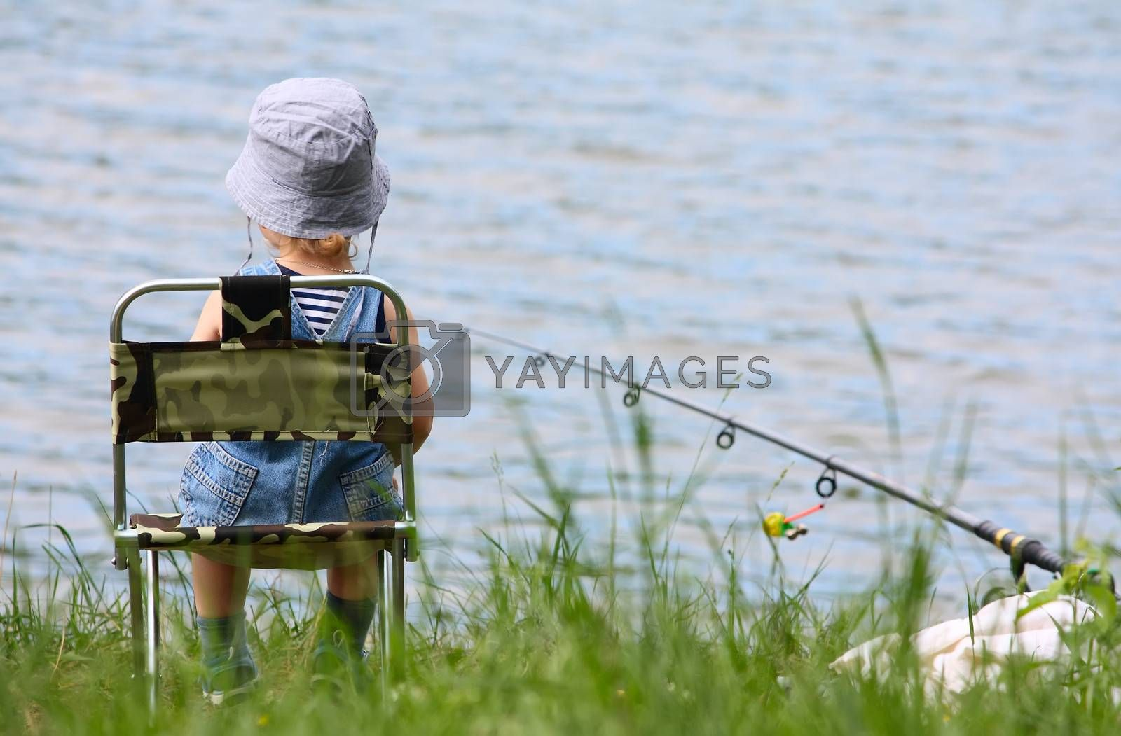 Little boy with fishng rod sitting near the lake