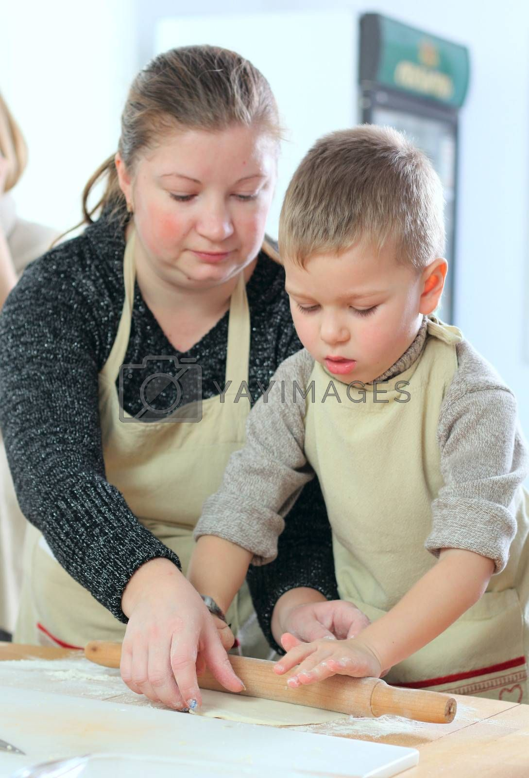 Little boy with his mother cooking at the kitchen