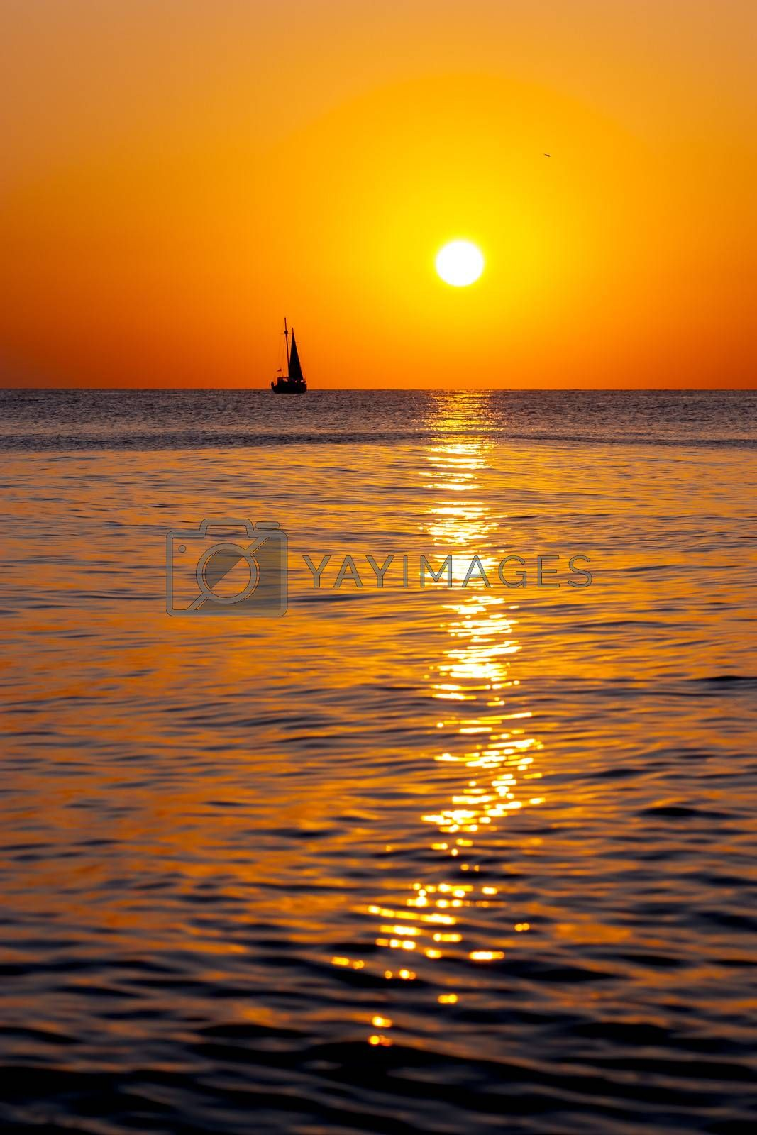 Single yacht in the sea at sunset