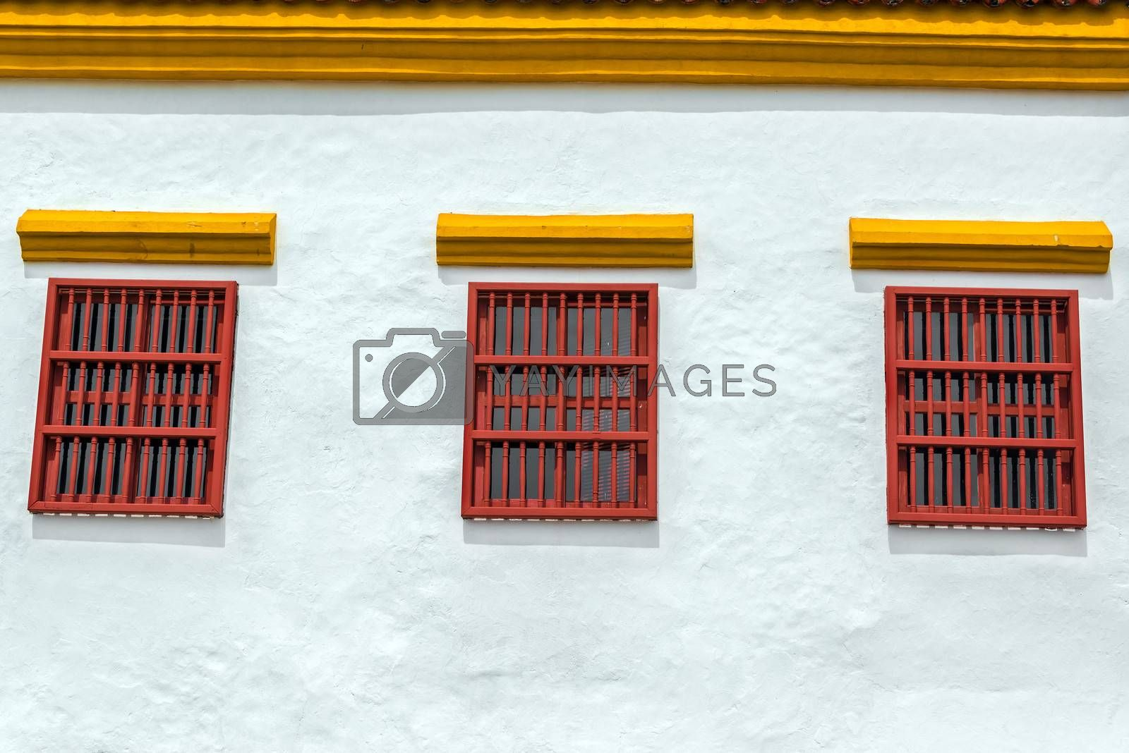 Three red windows on a white historic colonial building the center of Cartagena, Colombia