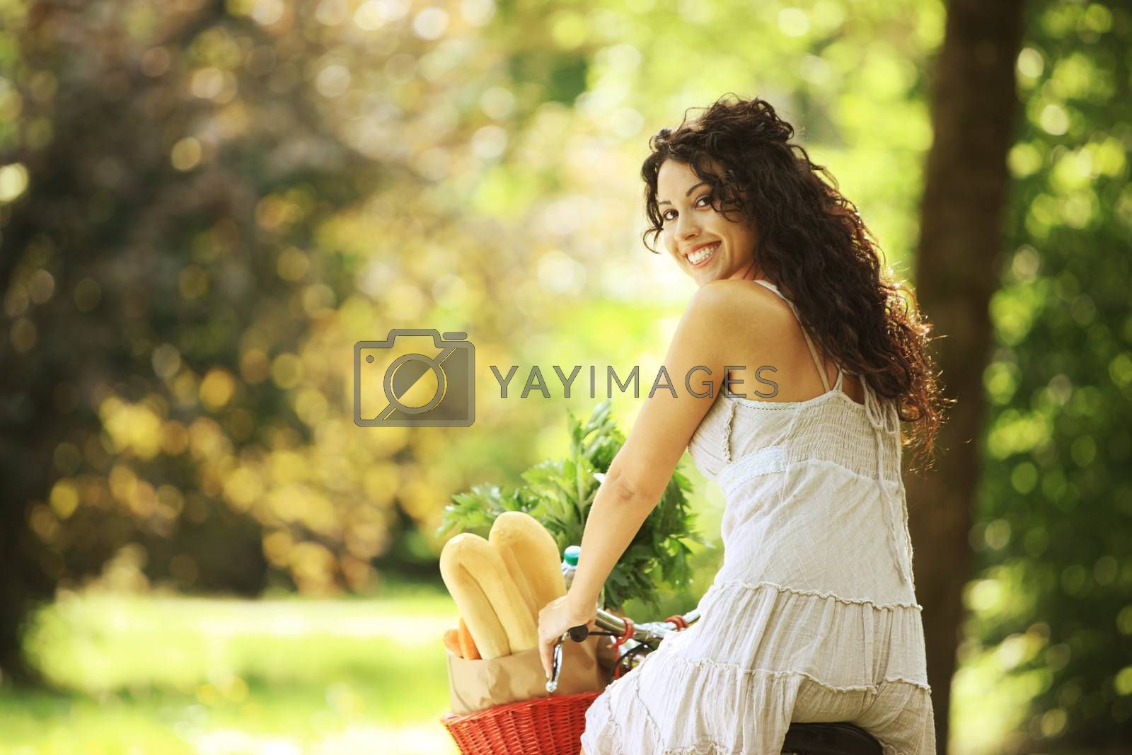 Portrait of a smiling young woman riding bicycle with groceries in basket