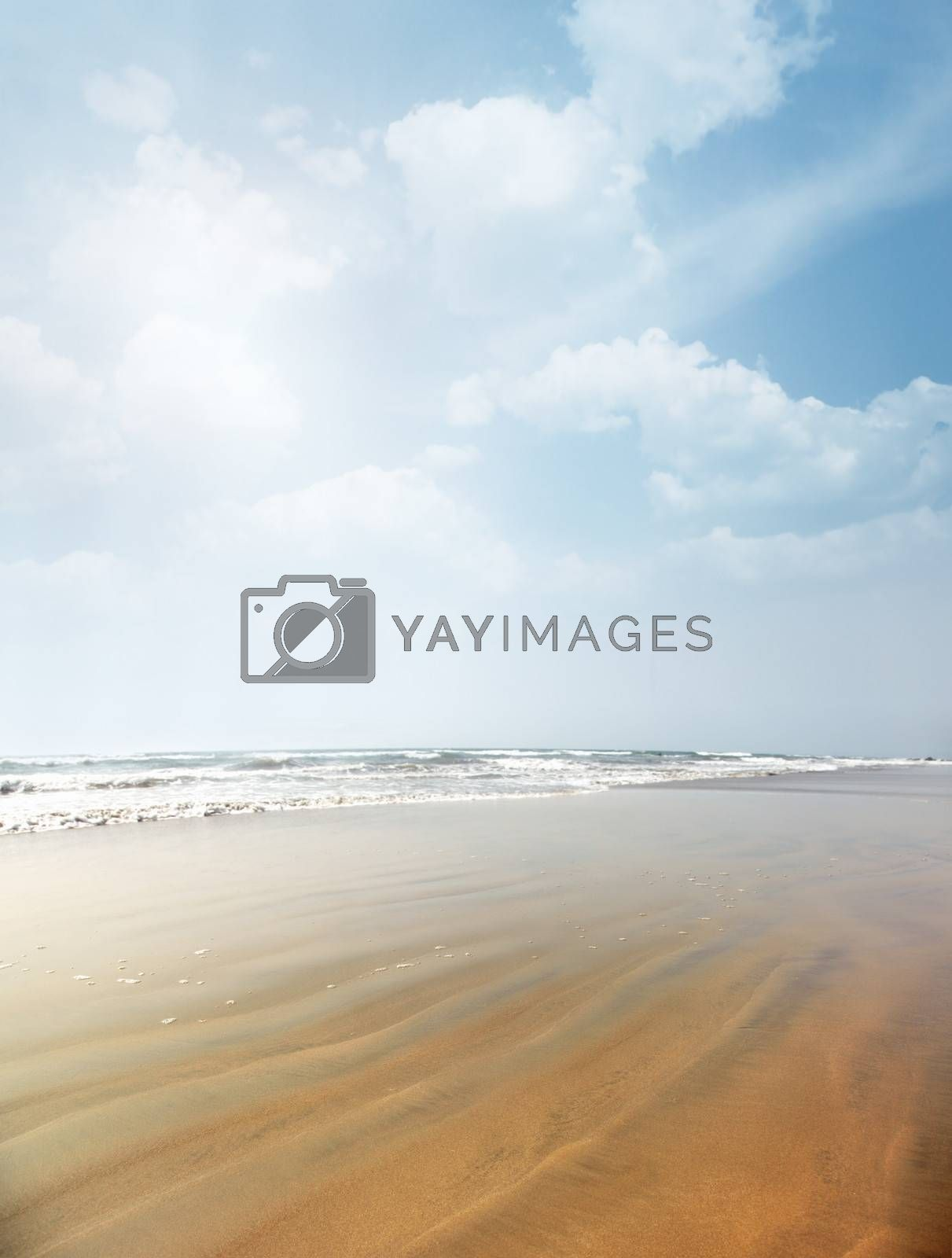 Vertical photo of the summer beach with rippled sand. Vibrant colors